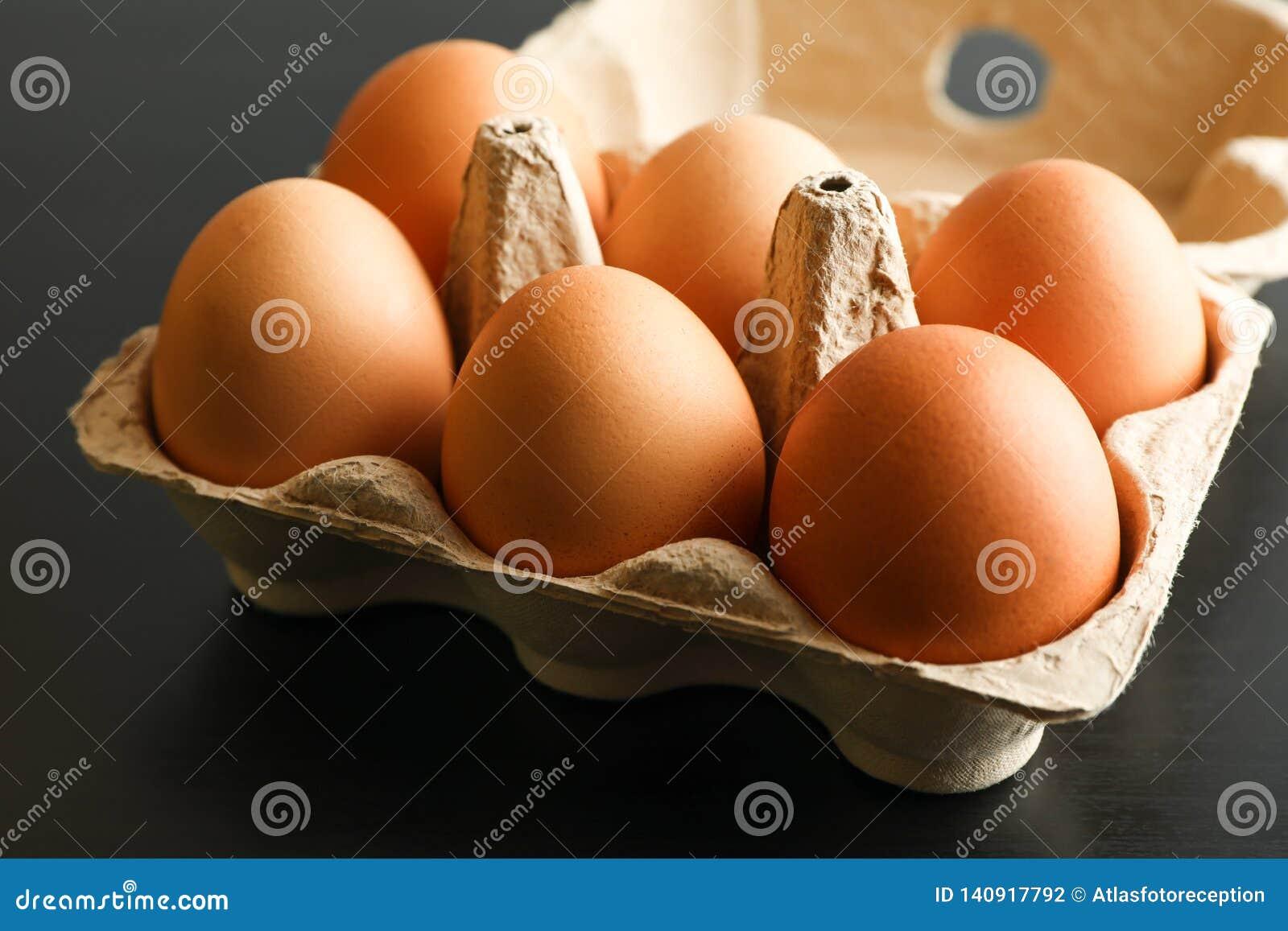 Uova del pollo in contenitore di cartone su fondo nero