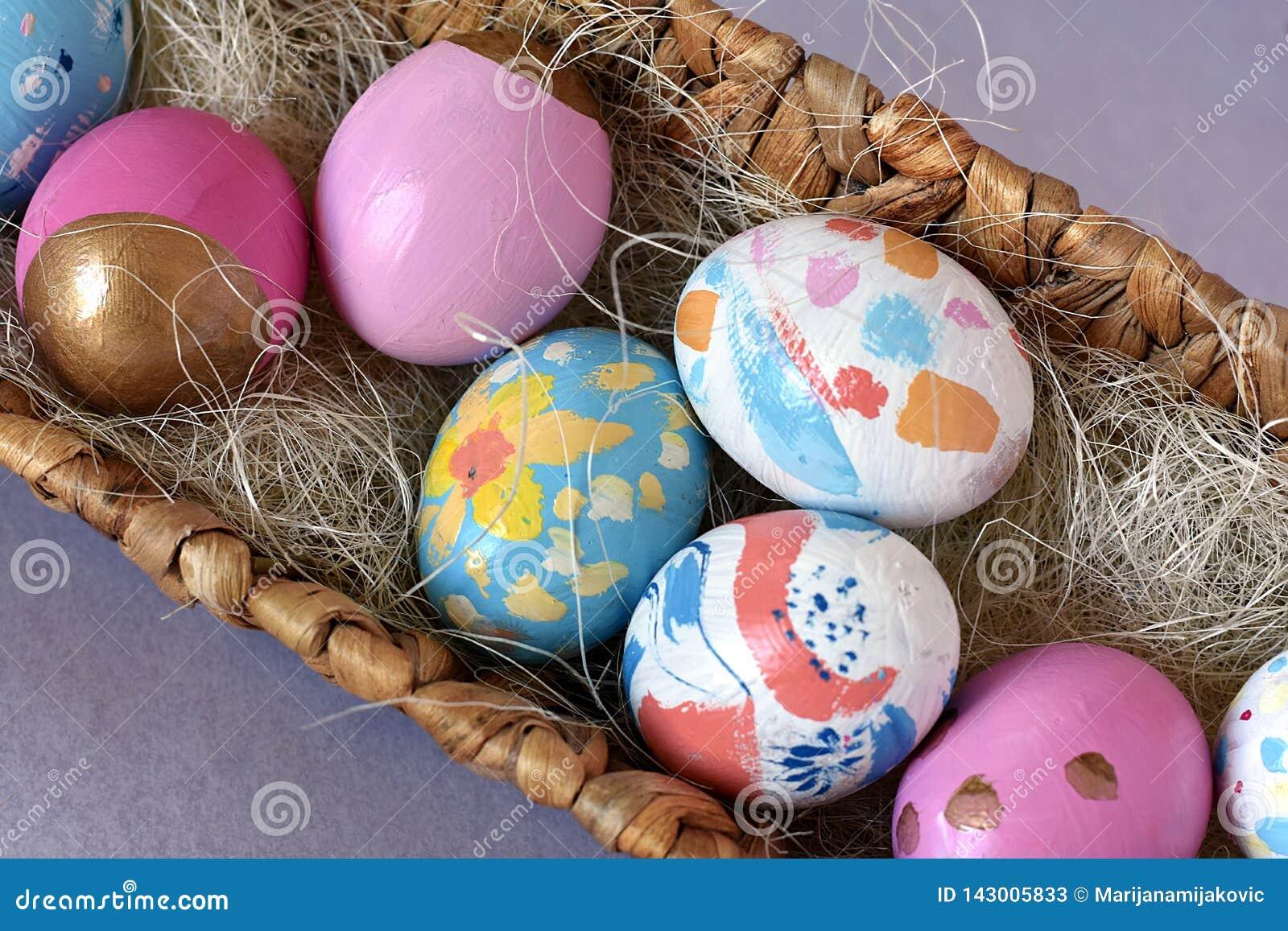 Uova di Pasqua colorate luminose in un nido di vimini, vista superiore