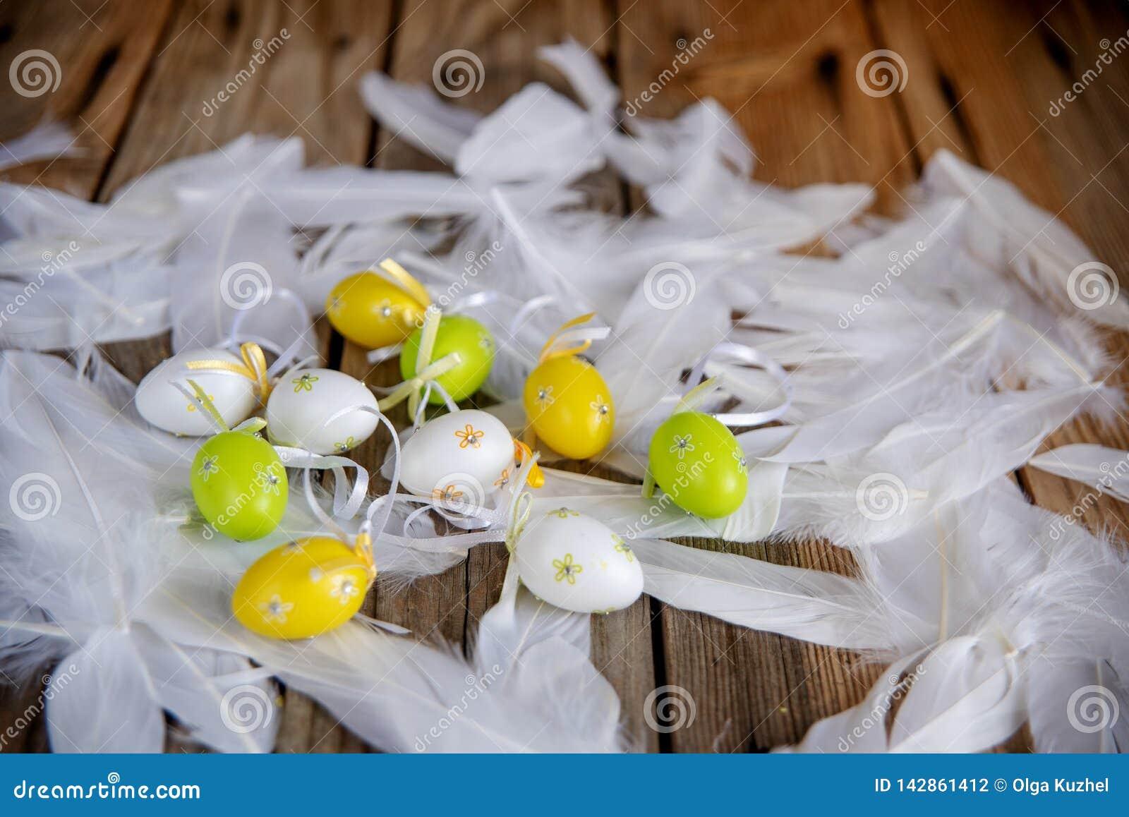 Uova di Pasqua decorative con le piume bianche su fondo di legno