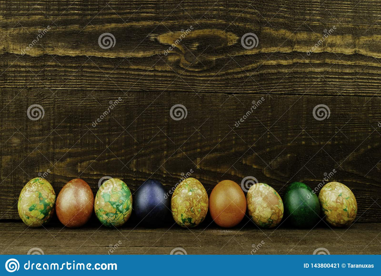 Uova di Pasqua in una fila su un fondo di legno marrone scuro, spazio della copia