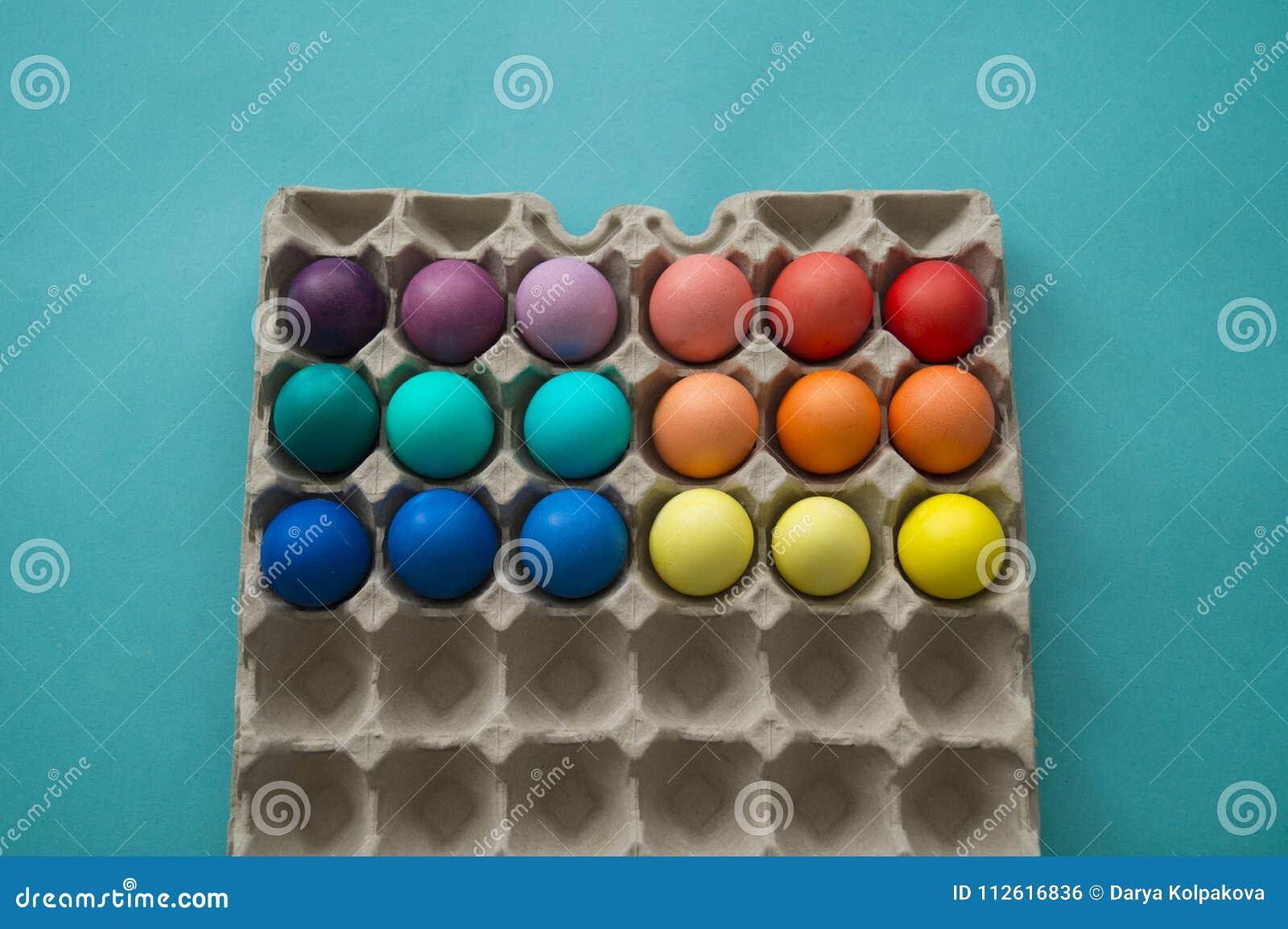 Uova di Pasqua variopinte tinte mano vibrante in una scatola delle uova del cartone osservata