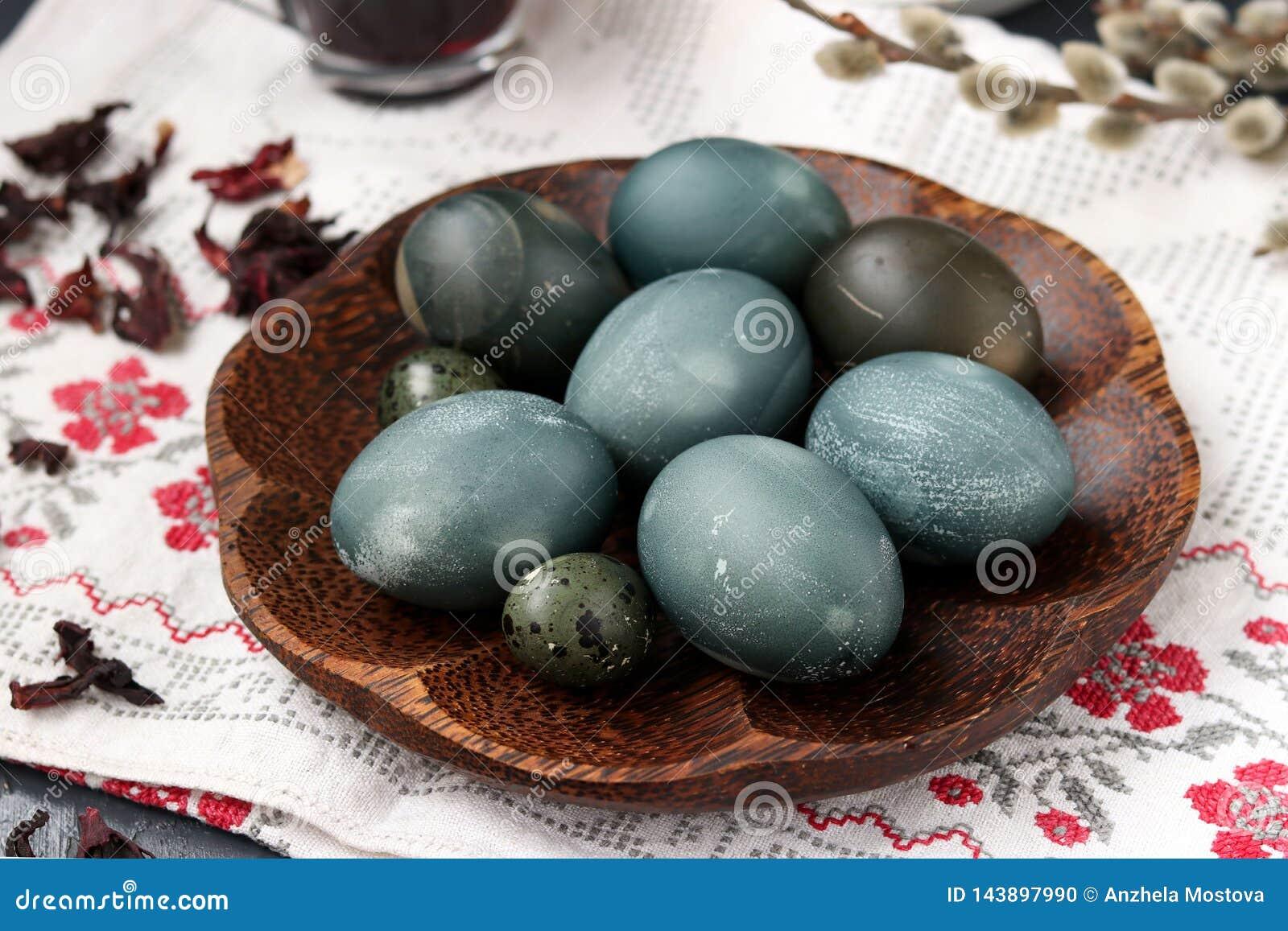 Uova di quaglia e del pollo su un piatto, dipinto con tè dai petali di una rosa o di un ibisco sudanese