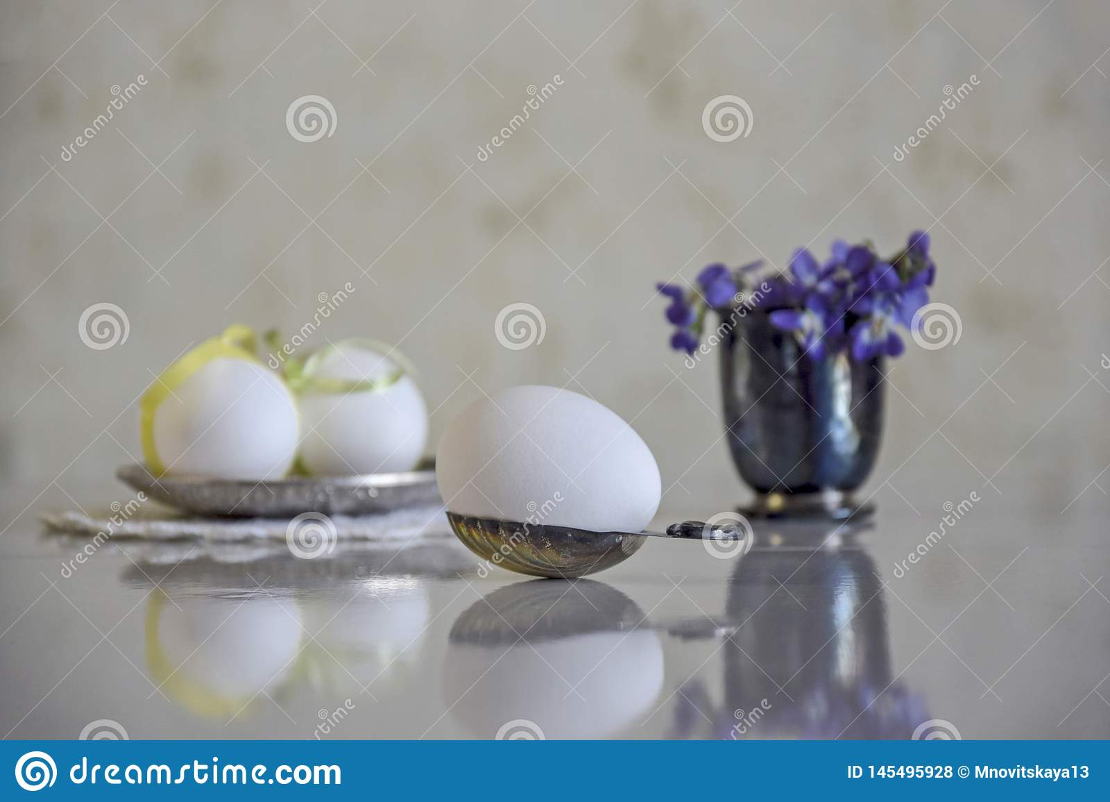 Uovo bianco in un cucchiaio d argento e un mazzo dei fiori della foresta
