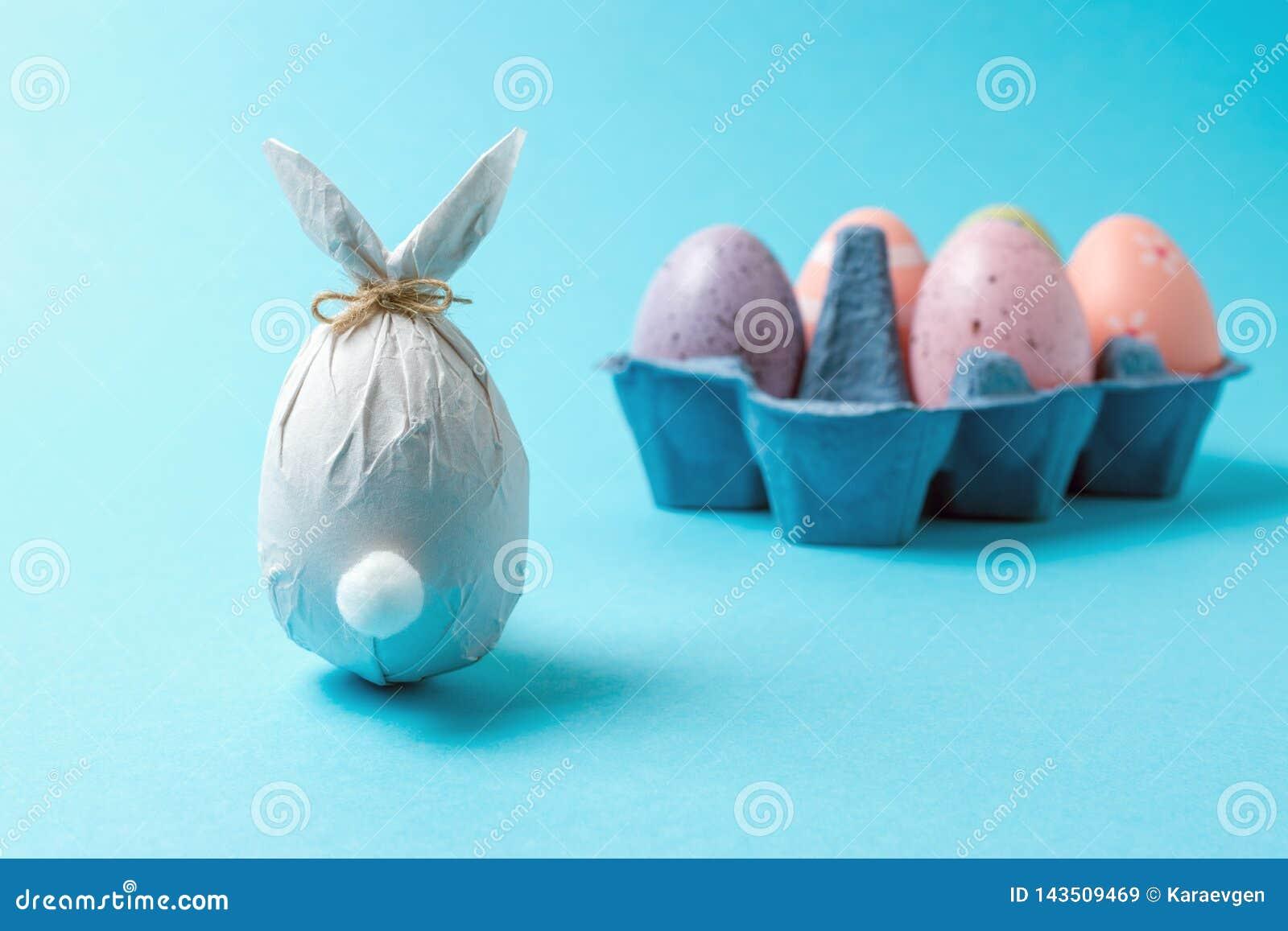 Uovo di Pasqua avvolto in una carta sotto forma di un coniglietto con le uova di Pasqua variopinte Concetto minimo di pasqua