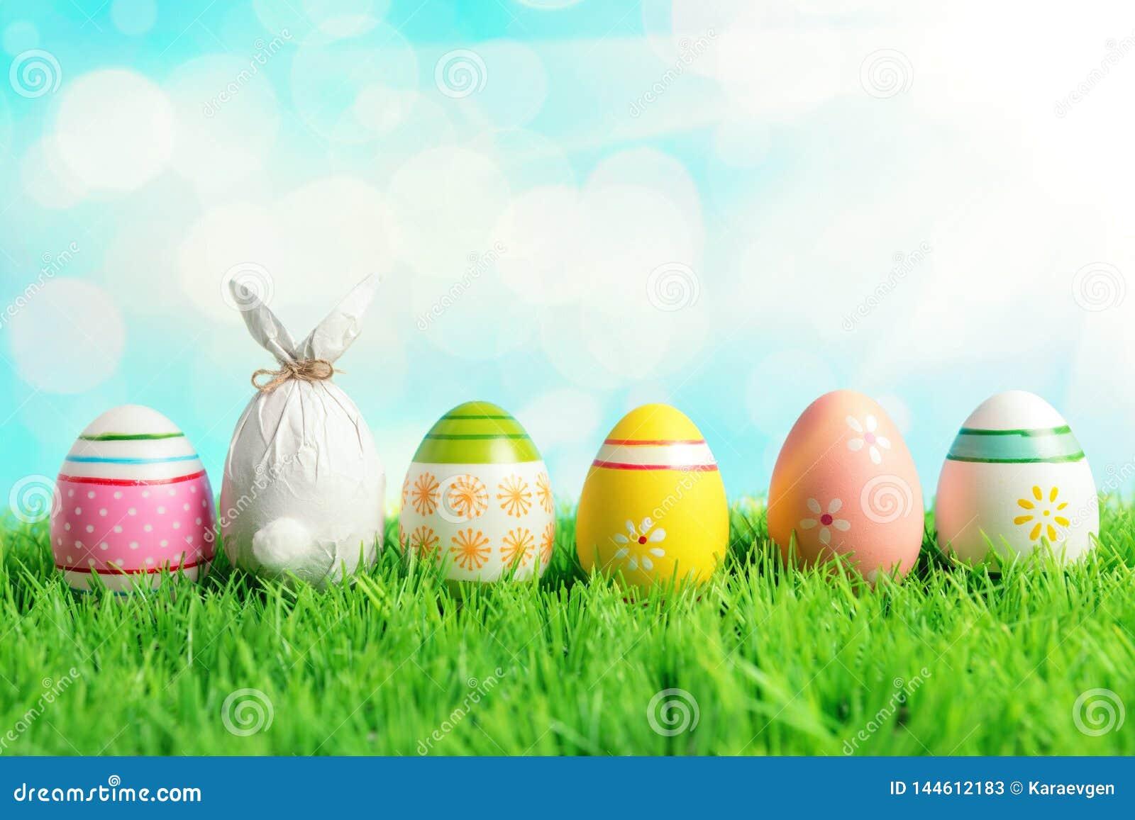 Uovo di Pasqua avvolto in una carta sotto forma di un coniglietto con le uova di Pasqua variopinte su erba verde Concetto di fest