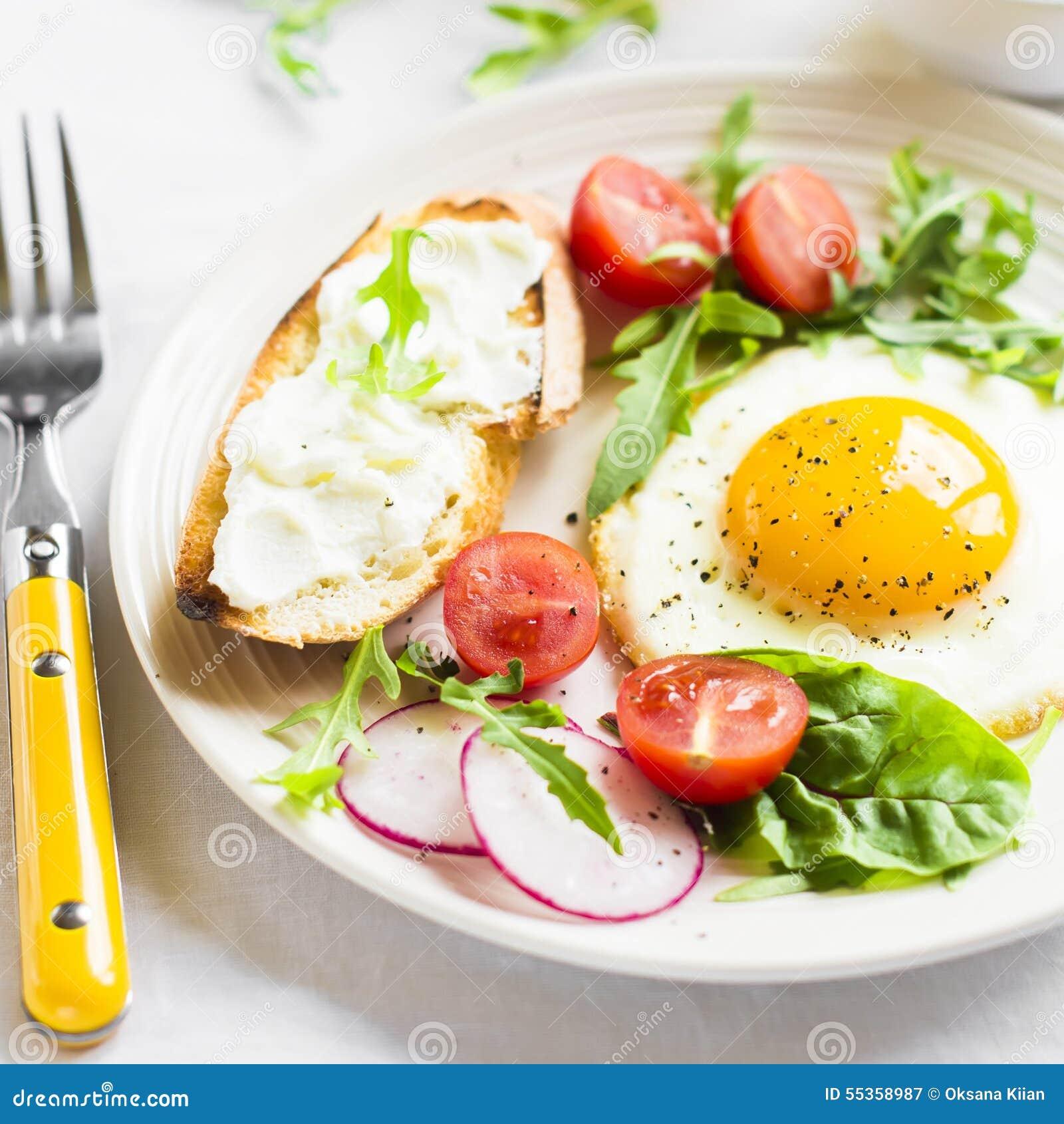 Uovo fritto, insalata di verdure e un panino arrostito del formaggio