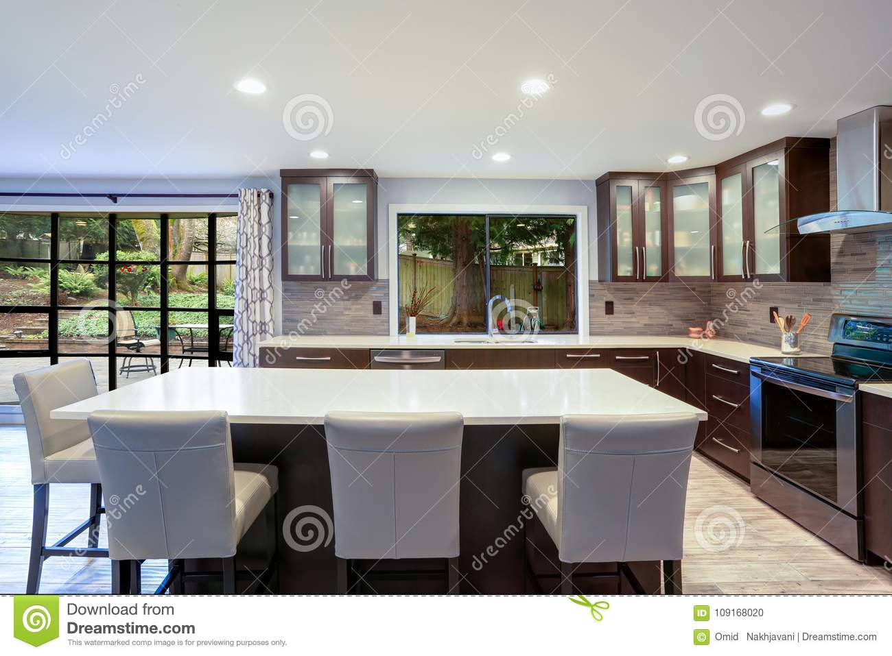 Updated contemporary kitchen room interior in white and brown tones.