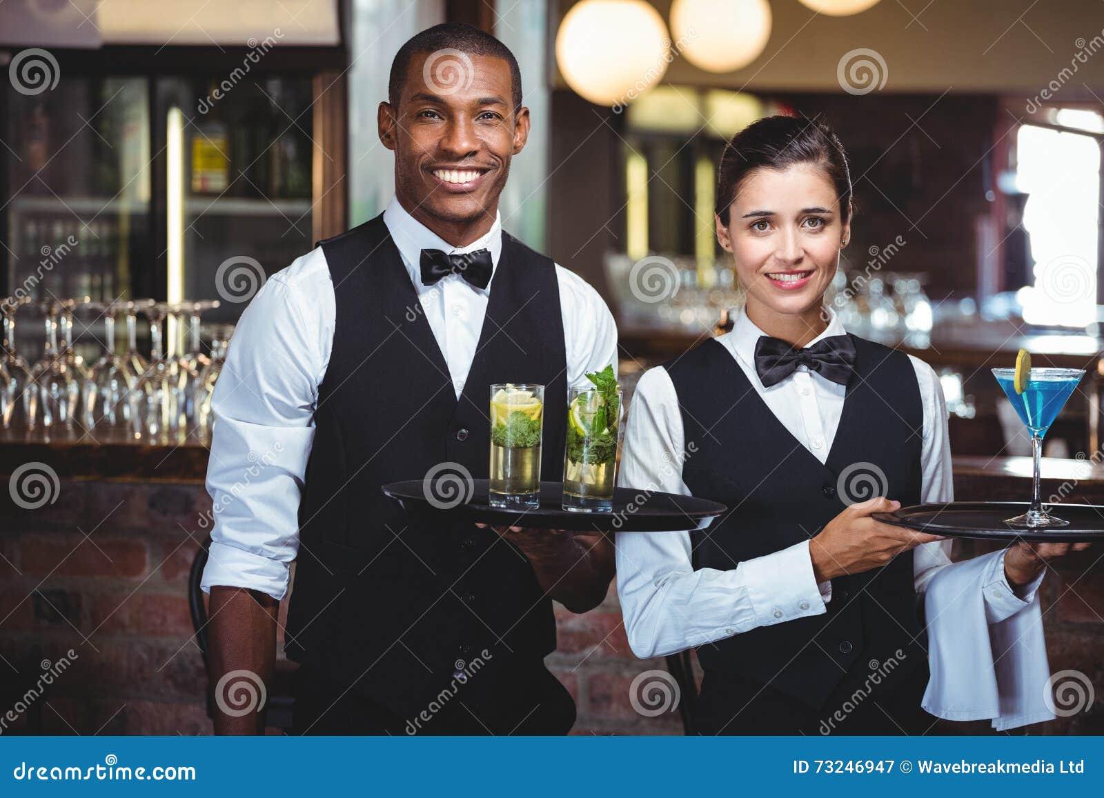 Uppassare och servitris som rymmer ett portionmagasin med exponeringsglas av coctailen
