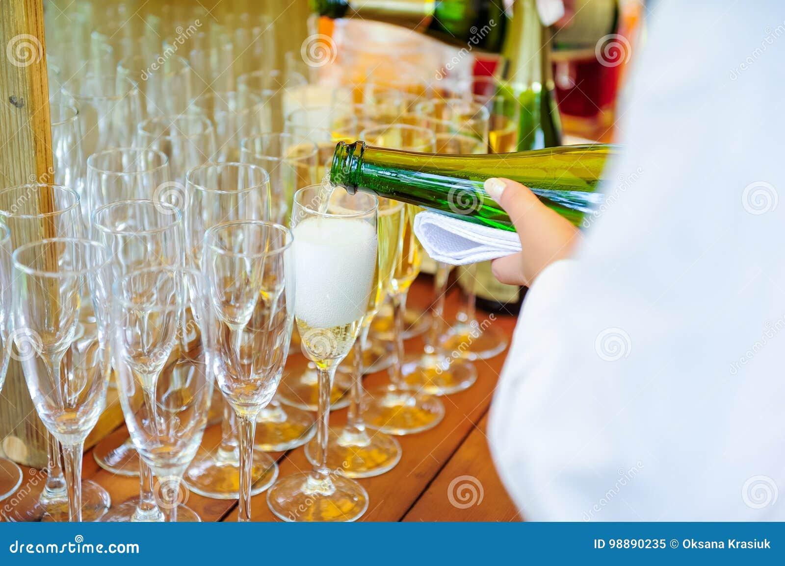 Uppassare som häller personlig portionChampagne i exponeringsglas Sköta om service på händelser, företags möte, parti, bröllop Se