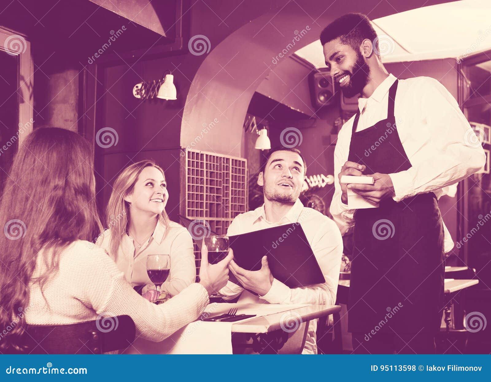 Uppassare som tar omsorg av vuxna människor på kafétabellen