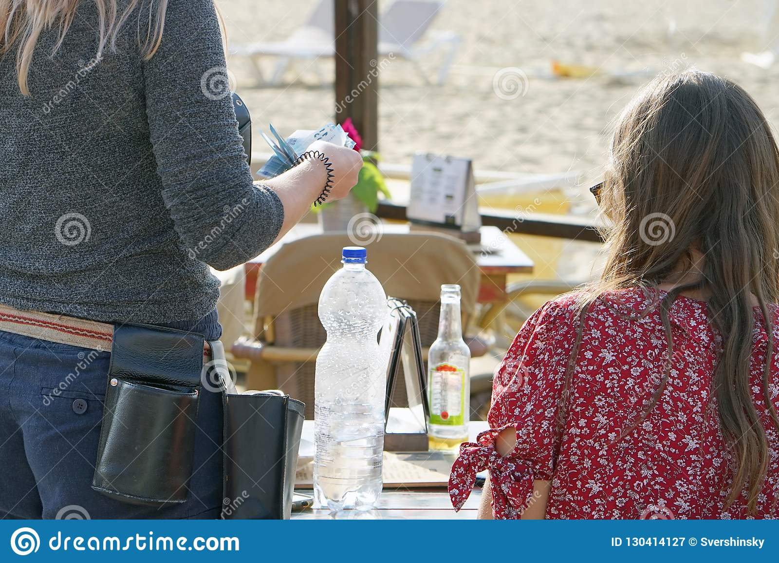 Uppassaren räknar kunden i ett kafé på stranden