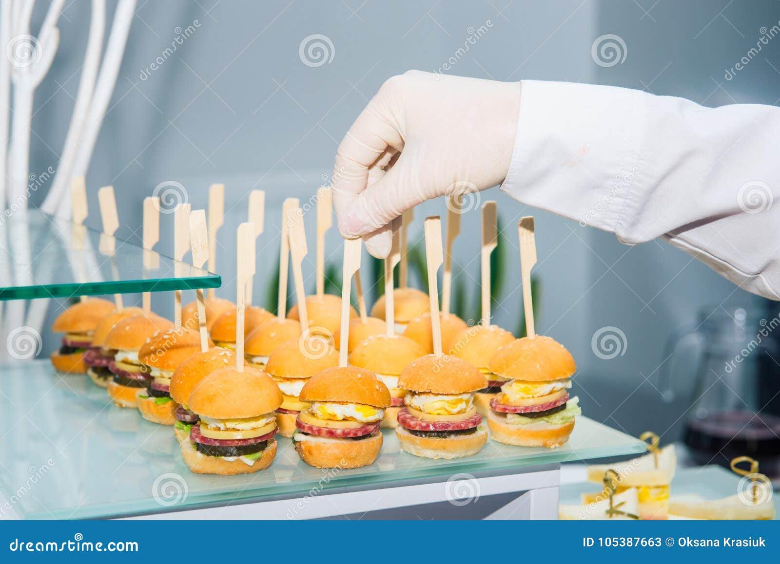 Uppassaren servering sköta om buffétabellen med mat och mellanmål för gäster av händelsen Äta middag begrepp för matberömparti