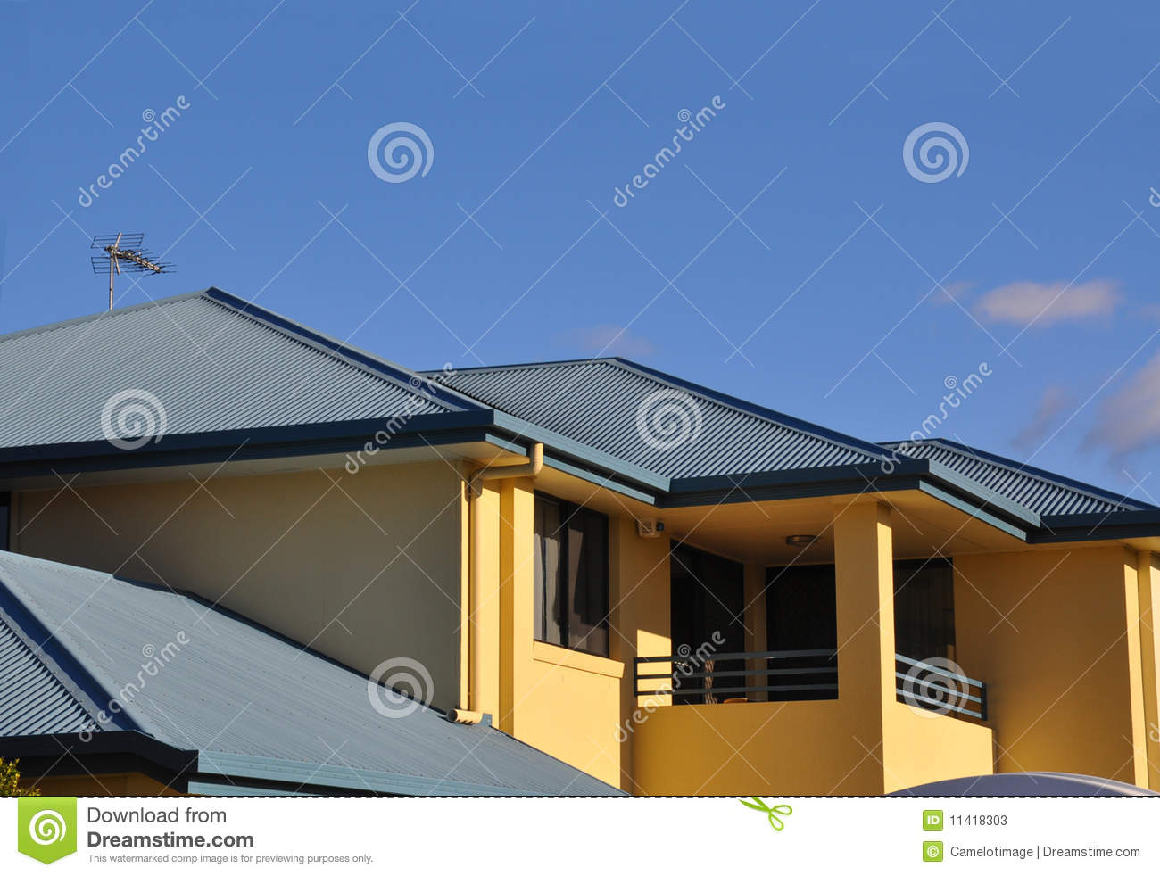 Upper storey of rendered house with metal roof