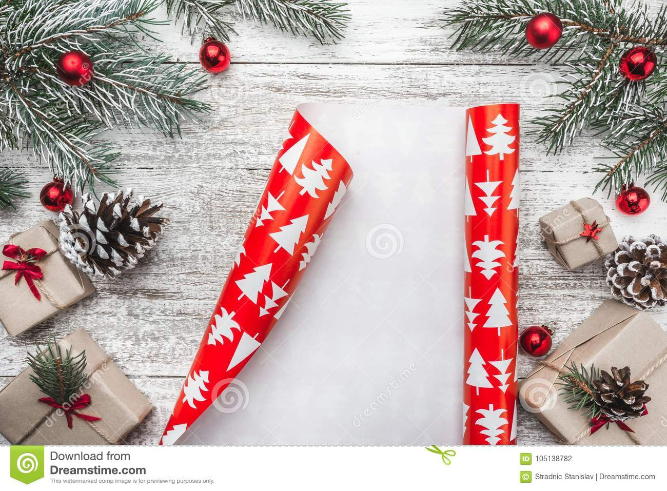Upper, top view, of Christmas presents on a wooden rustic background, decorated with evergreen branch.