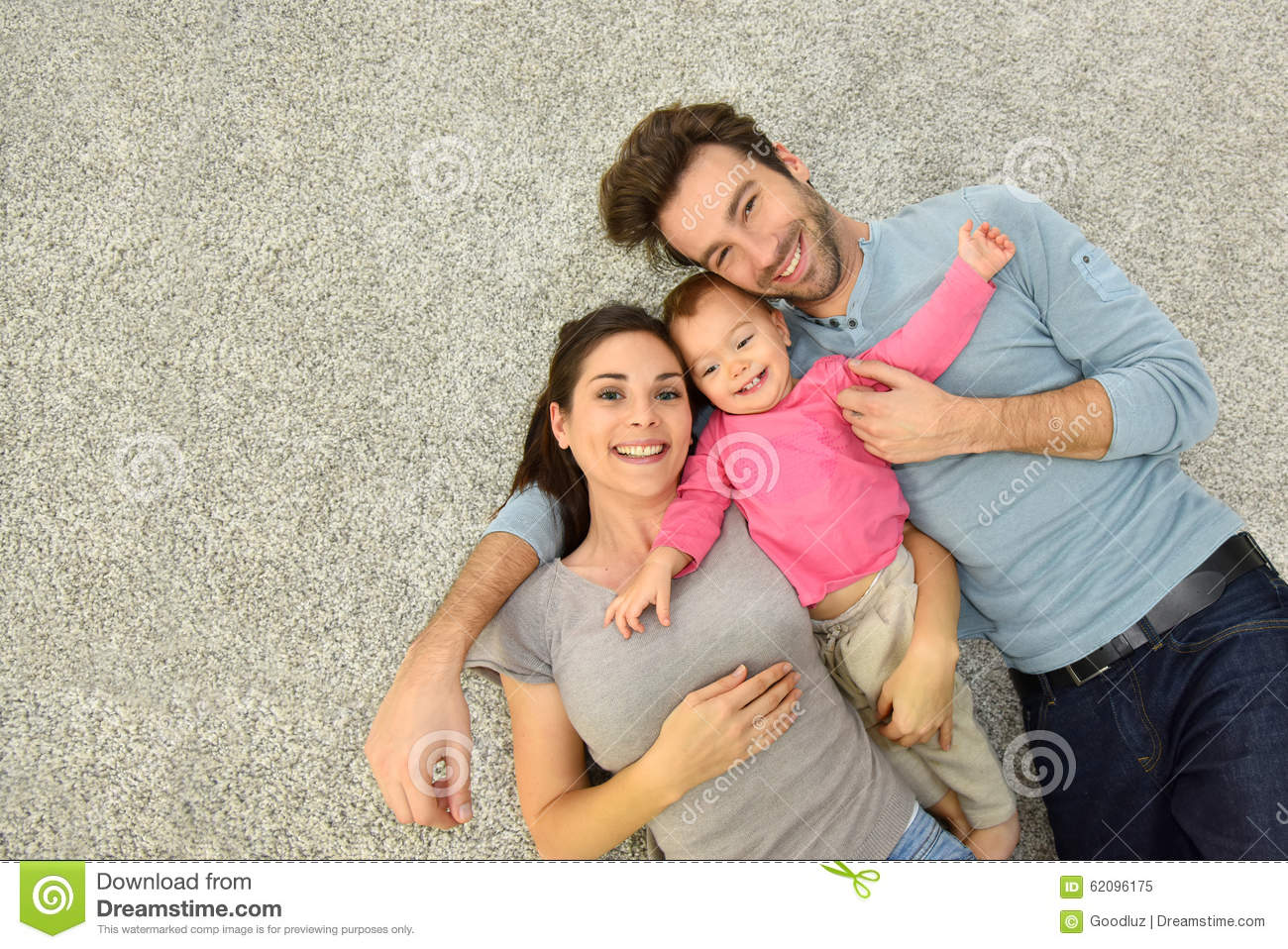 Upper View Of Family Of Three Laying On Carpet Floor Stock