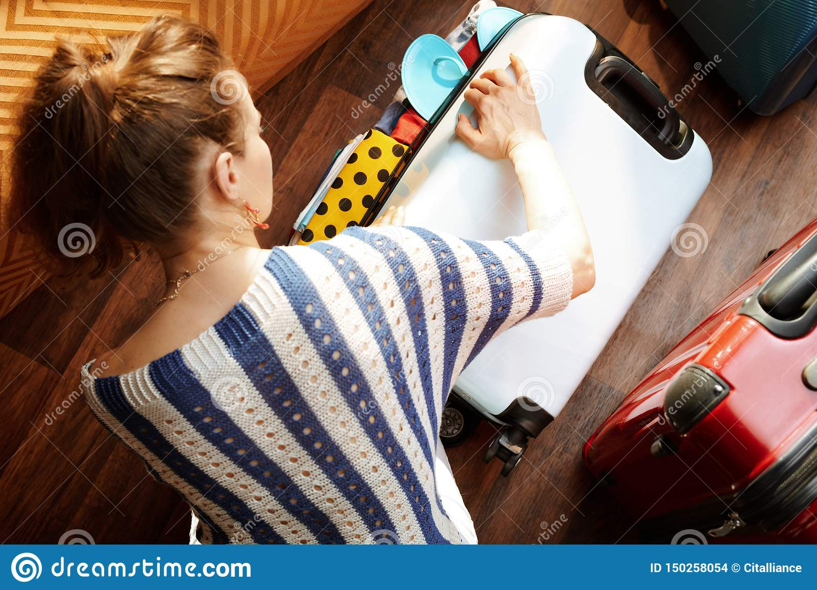 Modern woman closing over packed suitcase