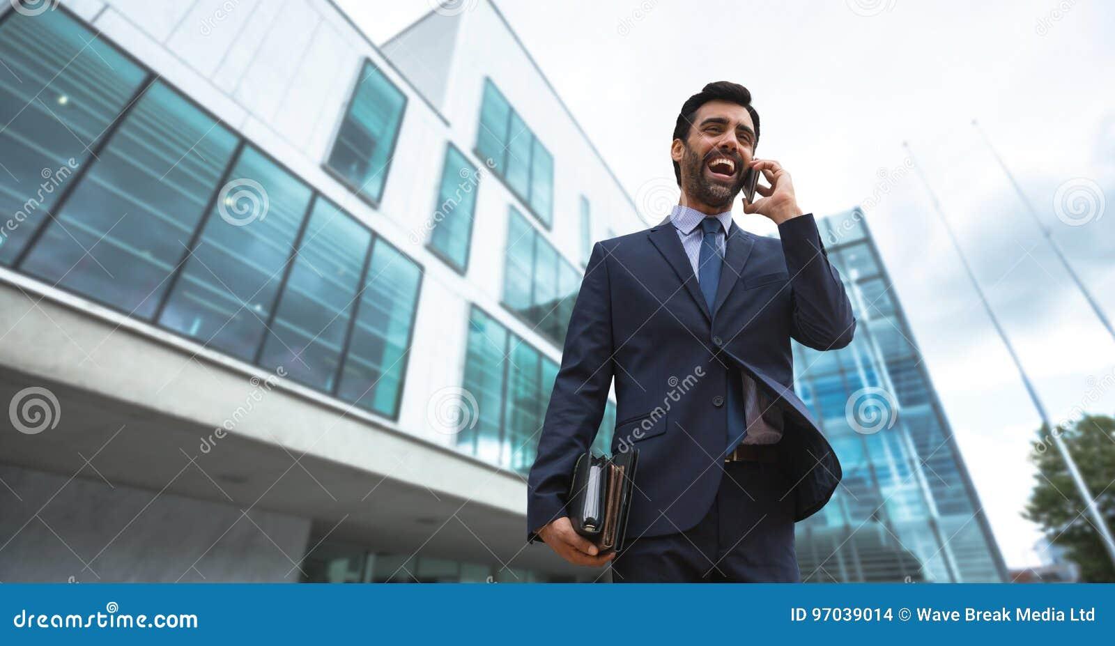 Upphetsad affärsman som talar på telefonen mot byggnadsbakgrund