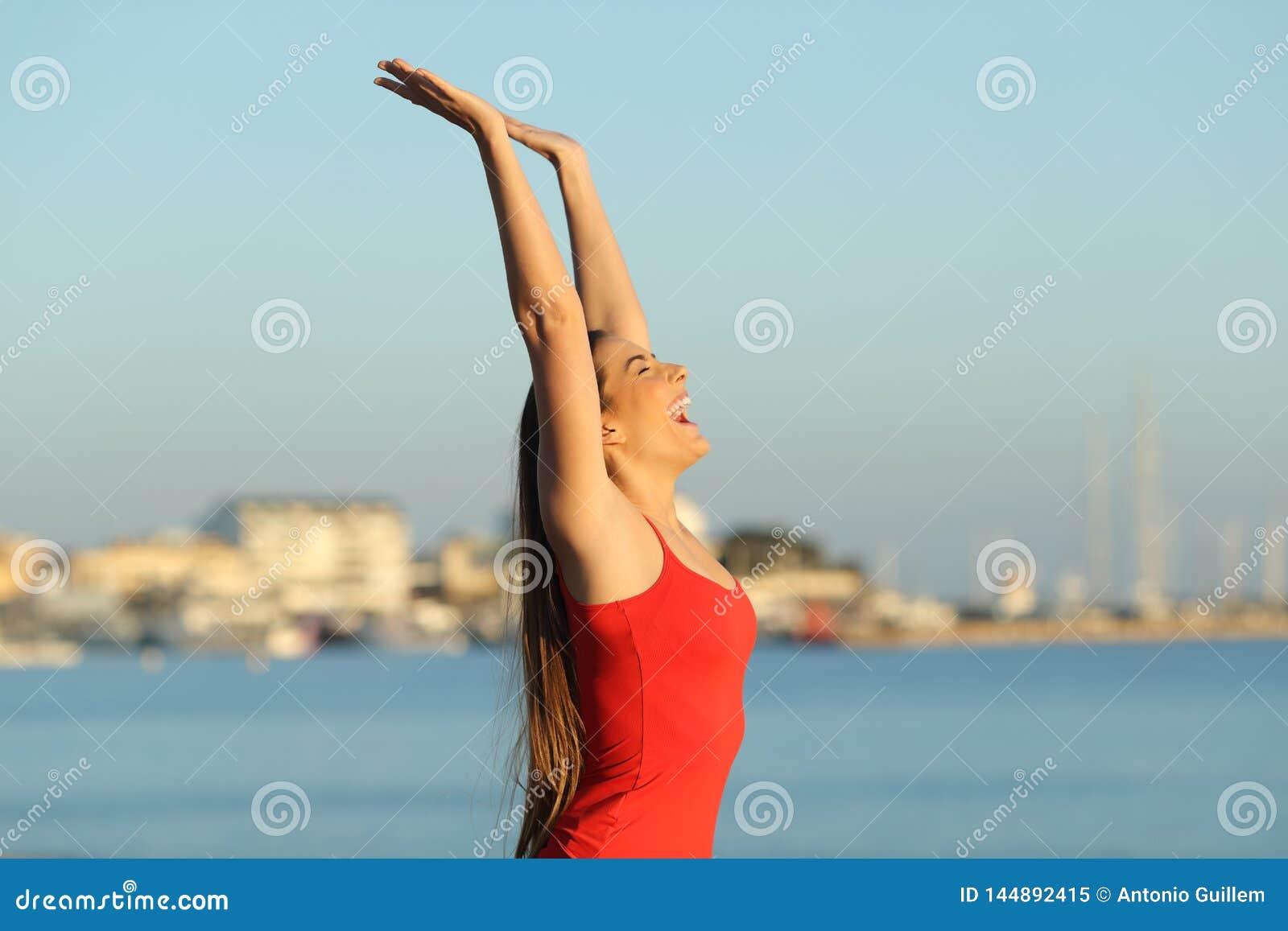 Upphetsad flicka i röd fira semester på stranden