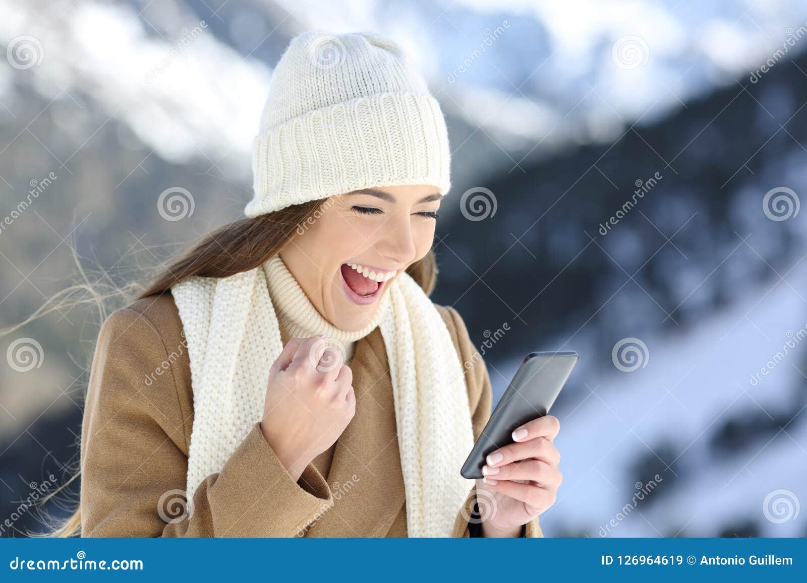 Upphetsad flicka som kontrollerar online-nyheterna i vinter