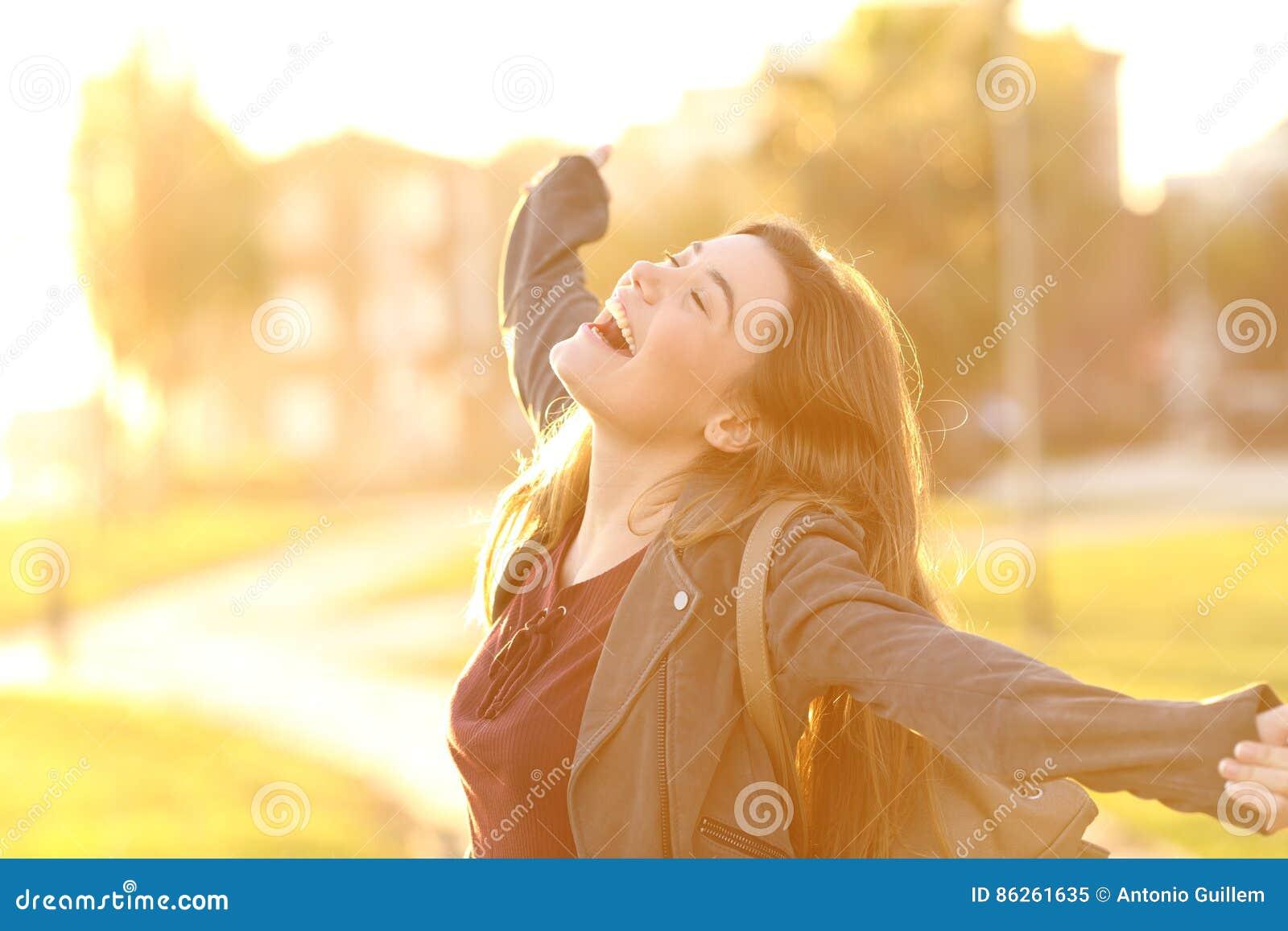Upphetsad flicka som lyfter armar i gatan