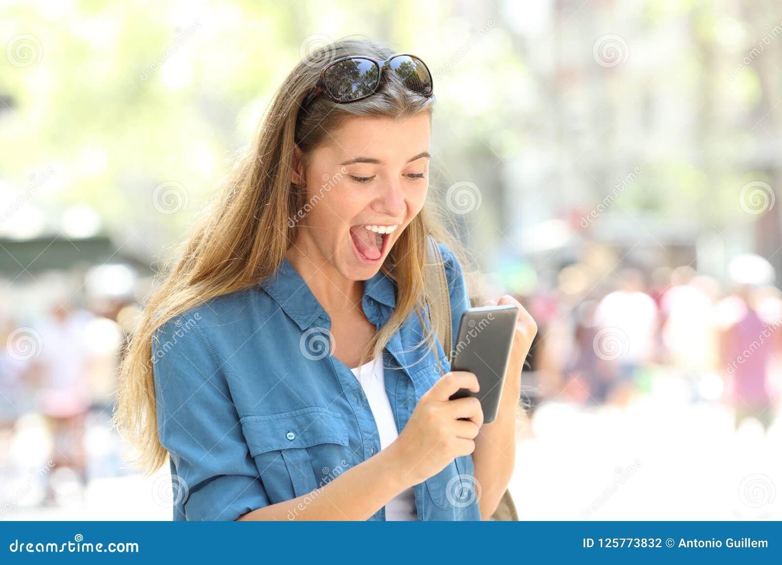 Upphetsad flicka som rymmer en smart telefon i gatan