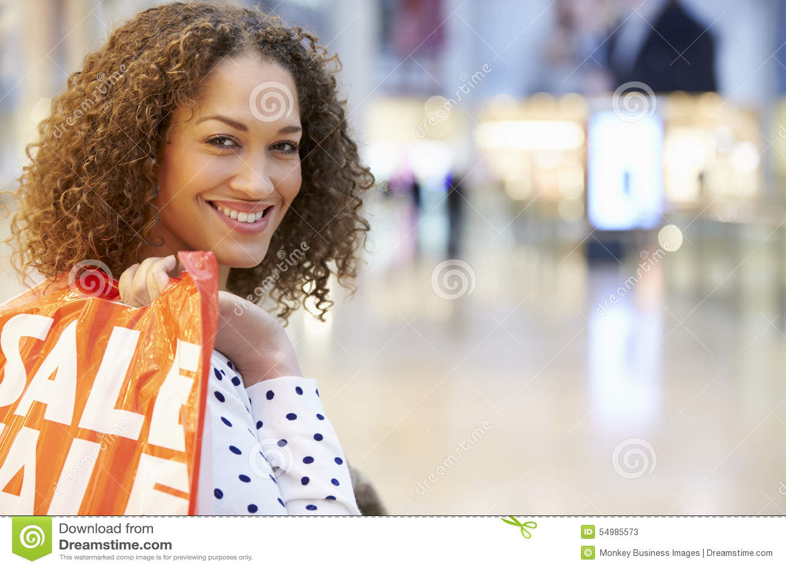 Upphetsad kvinnlig shoppare med Sale påsar i galleria