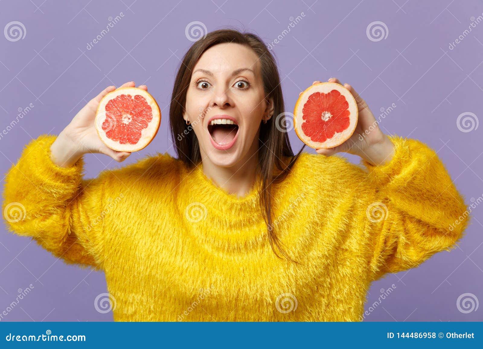 Upphetsad ung kvinna i pälströjan som håller öppna rymmande halfs för mun av den nya mogna grapefrukten som isoleras på violett p