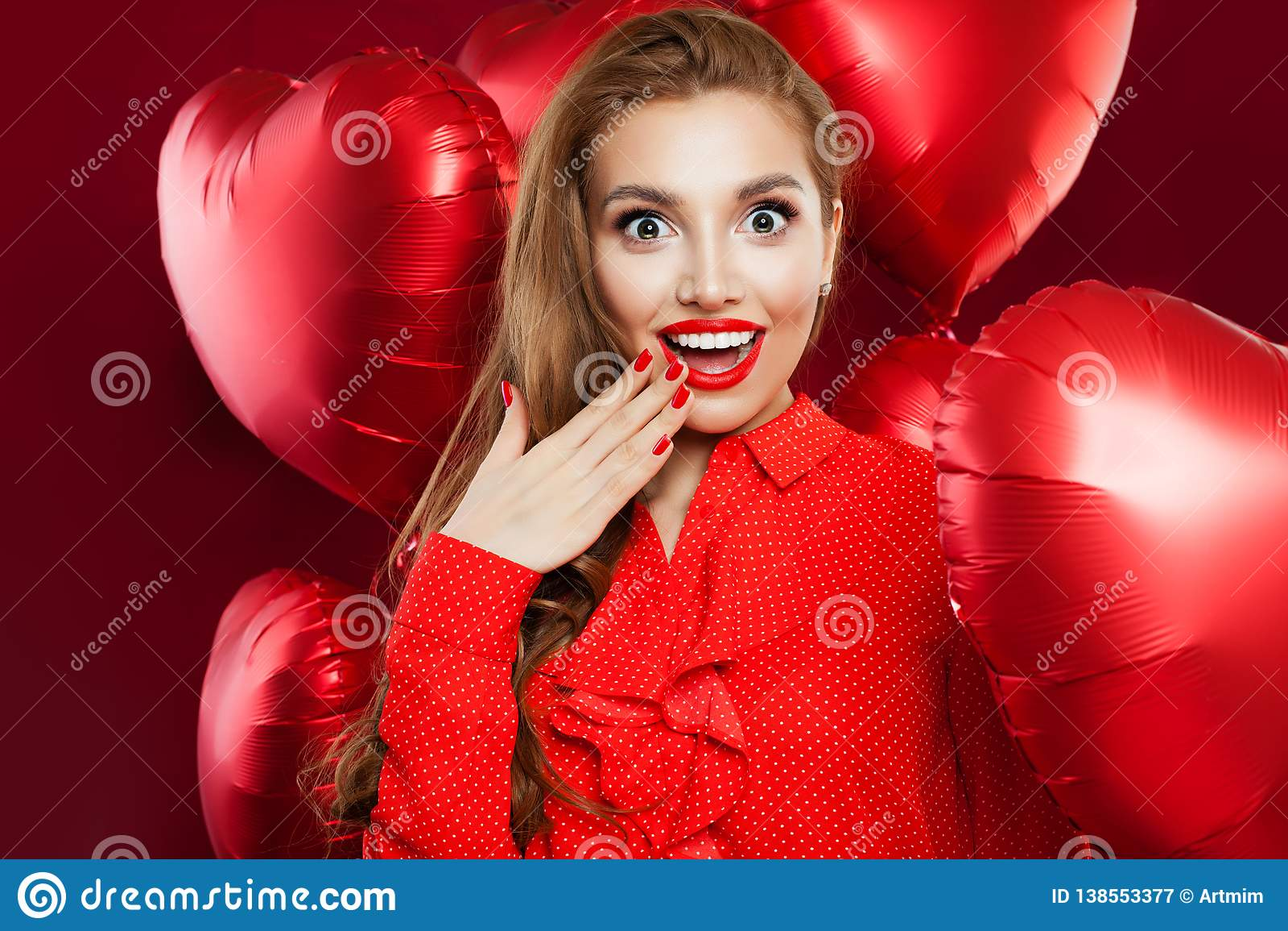 Upphetsad ung kvinna med röda hjärtaballonger Den förvånade flickan med röd kantmakeup, långt lockigt hår andExcited flickan på r