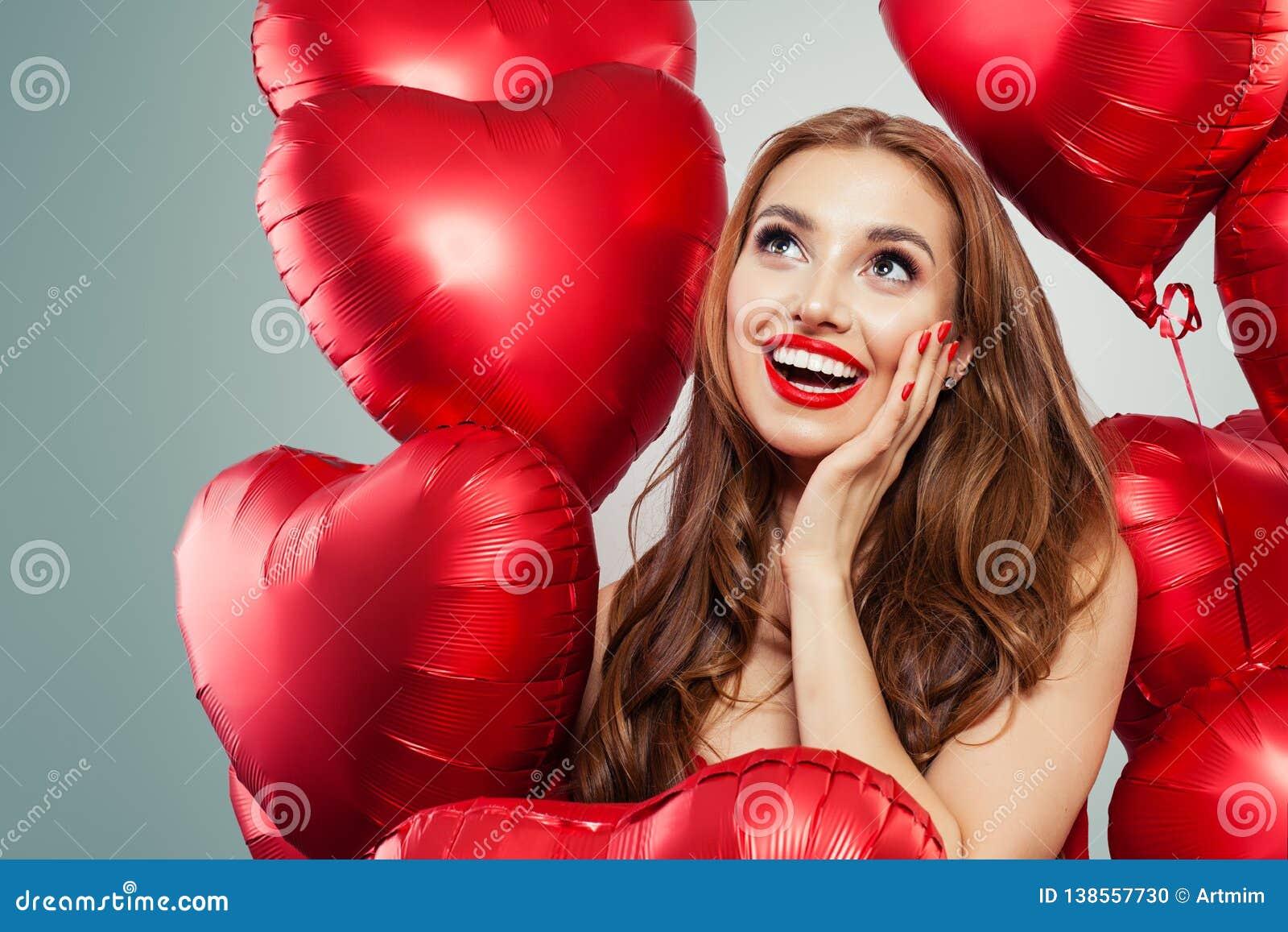 Upphetsad ung kvinna som rymmer röd hjärta för ballonger Förvånad flicka med röd kantmakeup, långt lockigt hår och gulligt leende