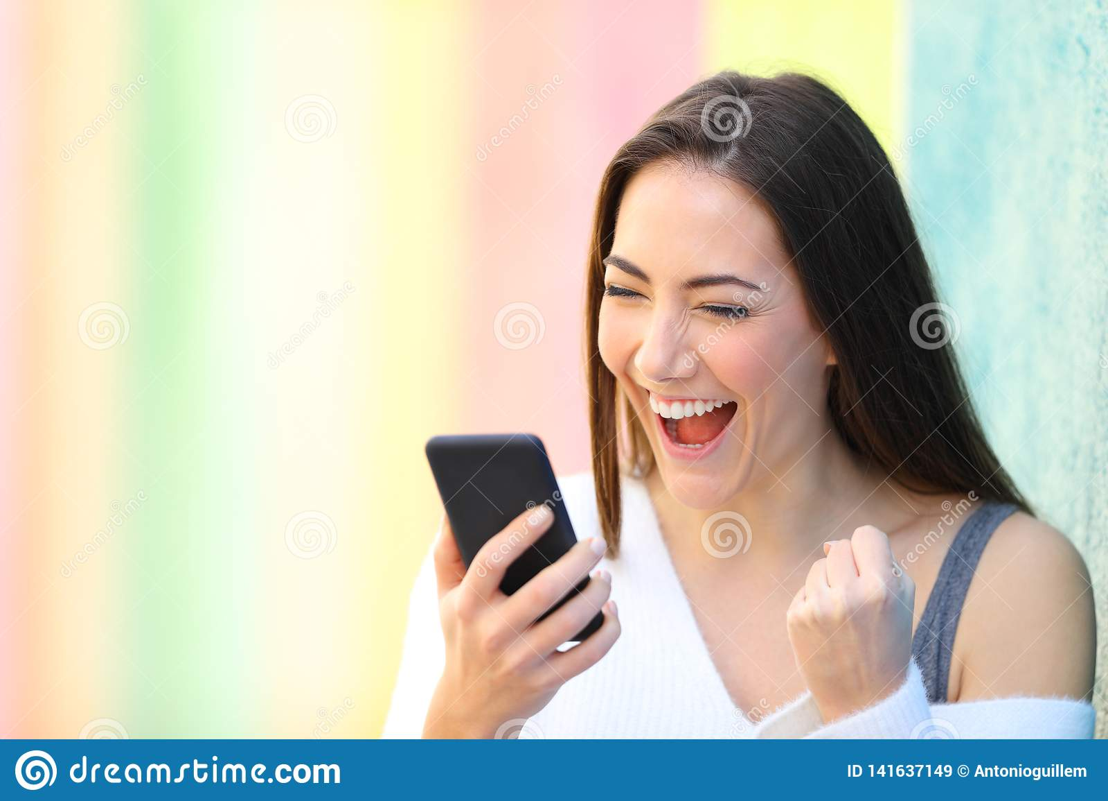 Upphetsade flickaläsninggoda nyheter på telefonen i en färgrik gata