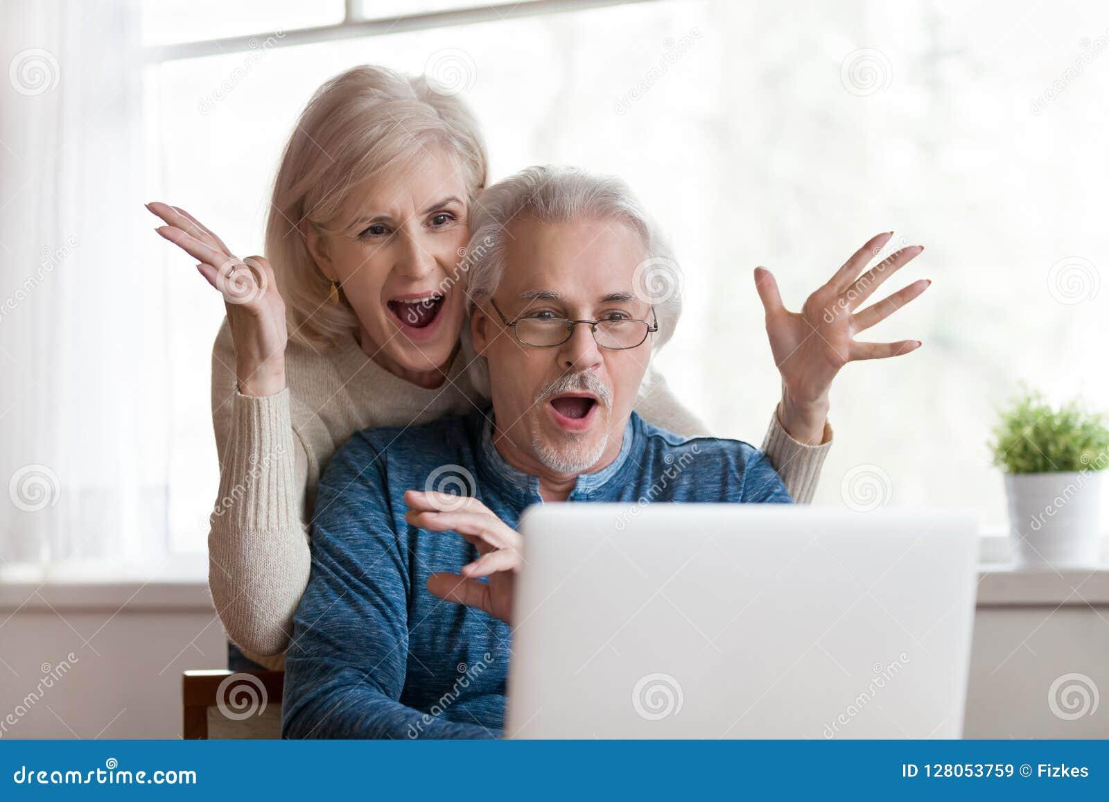 Upphetsade höga par som ser bärbara datorn som förvånas av goda nyheter