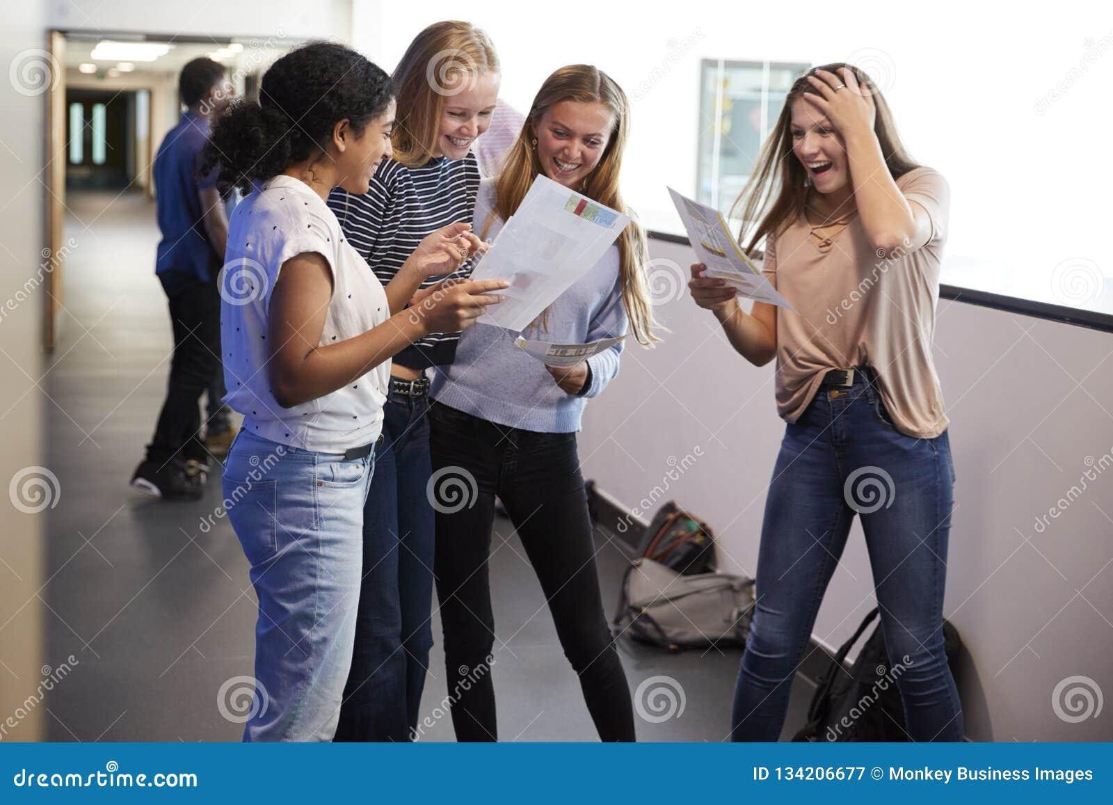 Upphetsade kvinnliga tonårs- högstadiumstudenter som firar examenresultat i skolakorridor