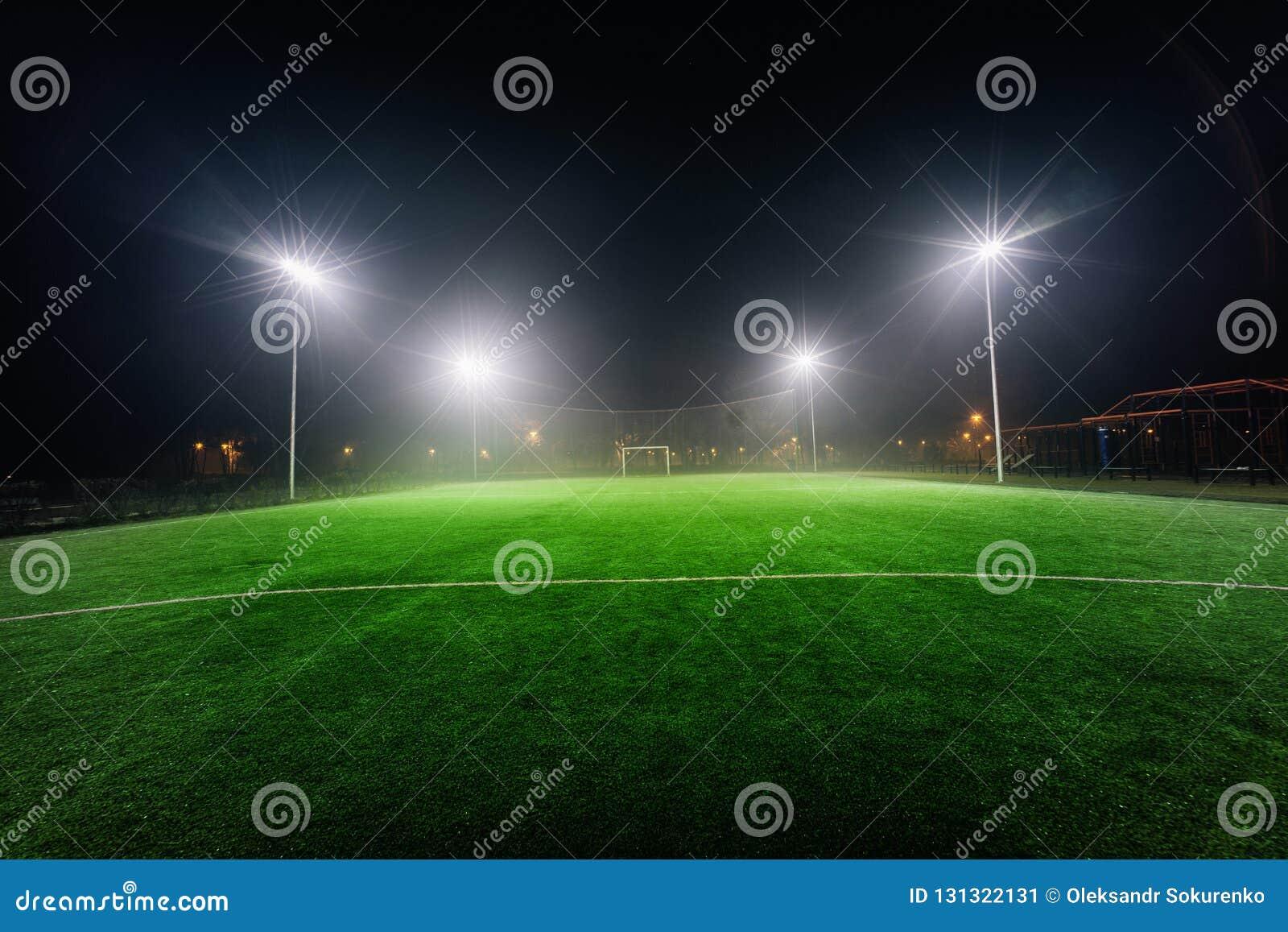Upplyst fotbolllekplats med grönt gräs