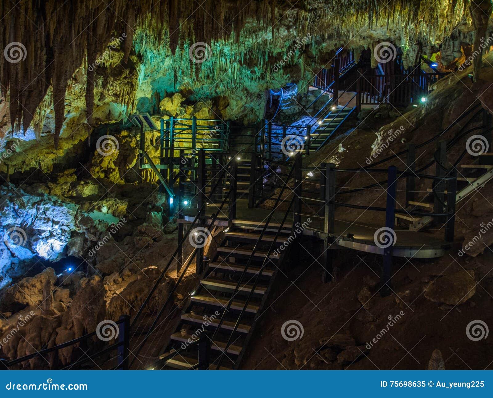 Upplysta stalaktit och stalagmit i den Ngilgi grottan i Yallingup