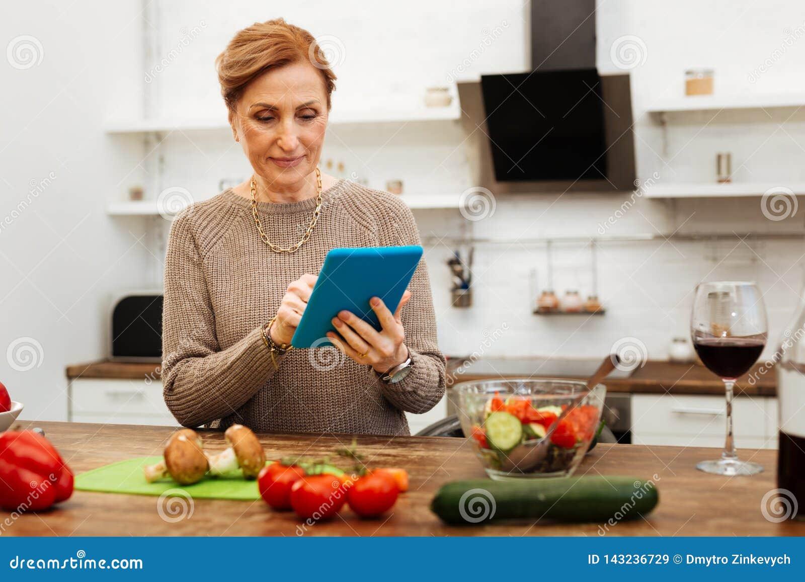Uppmärksam angenäm dam som blir i kök och bär hennes minnestavla