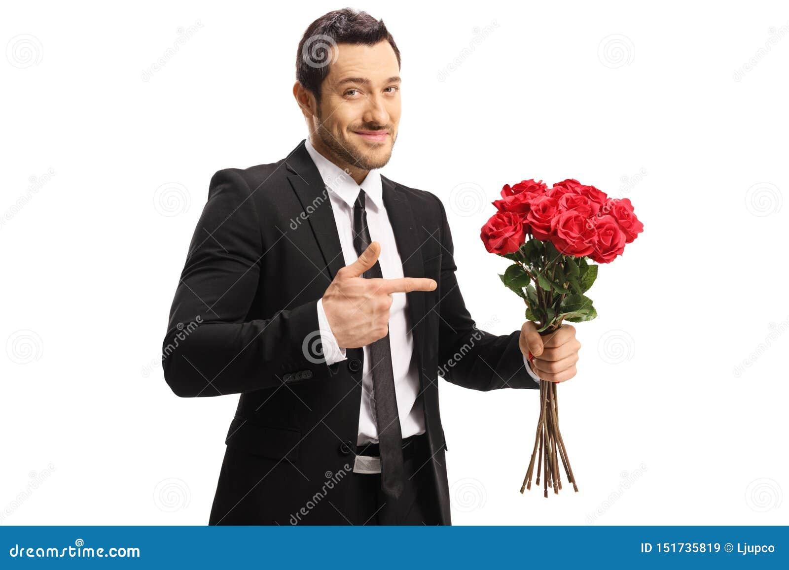 Uppnosig stilig ung man som rymmer en grupp av röda rosor och pekar på dem