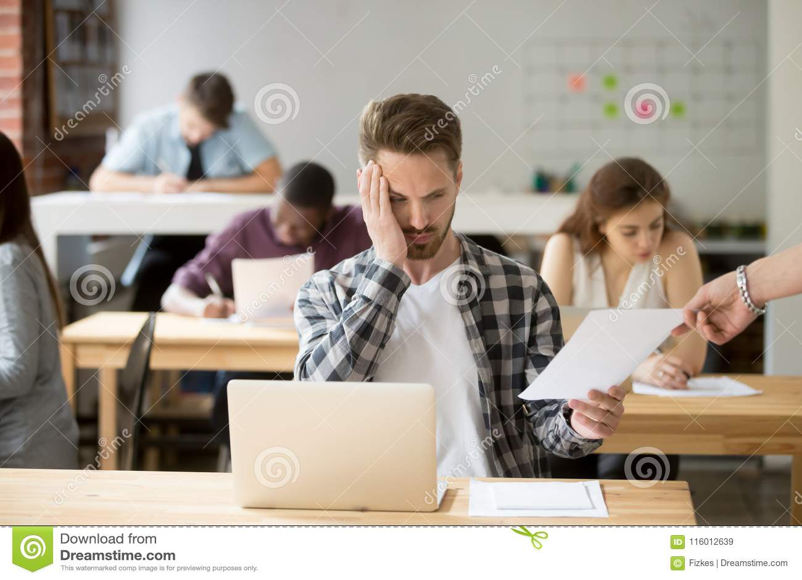 Uppriven manlig student som är stressad om examenfläck