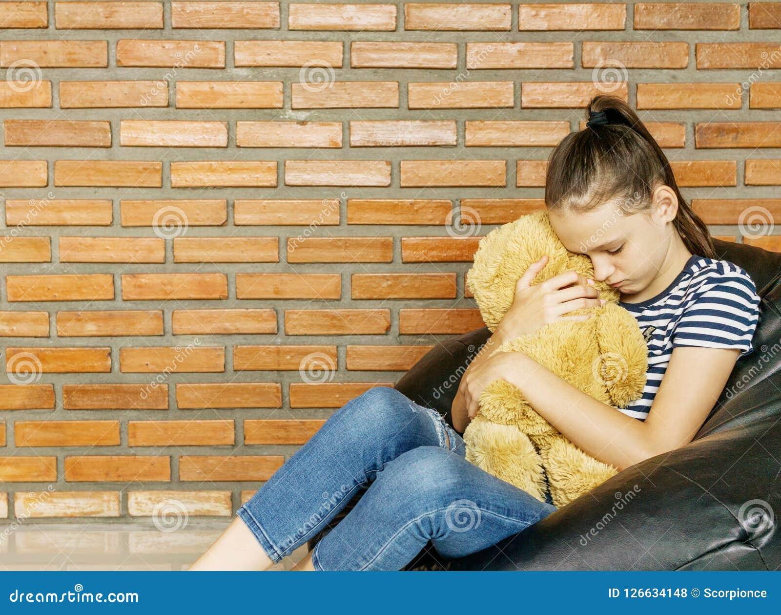 Upprivet caucasian tonårigt flickasammanträde i leksak för björn för nalle för kram för stol för påse för svart böna stor brun mo