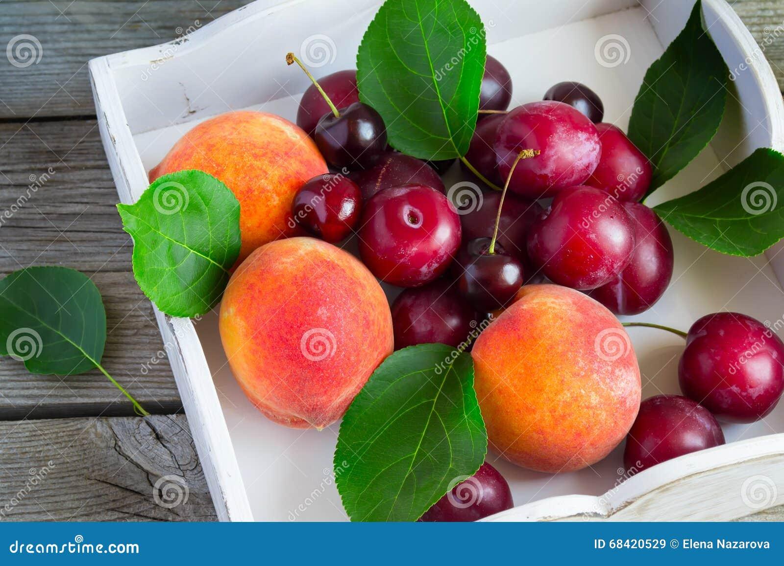 Uppsättning av frukt: persikor plommoner, körsbär på ett vitt magasin