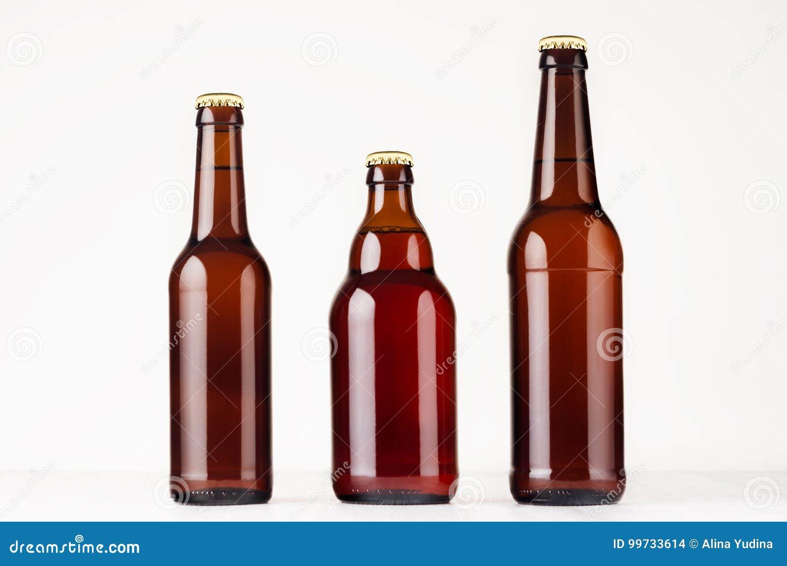 Uppsättning av olik brun ölflaskaåtlöje 500ml och 330ml upp Mall för annonsering, design som brännmärker identitet på vitt trä ta