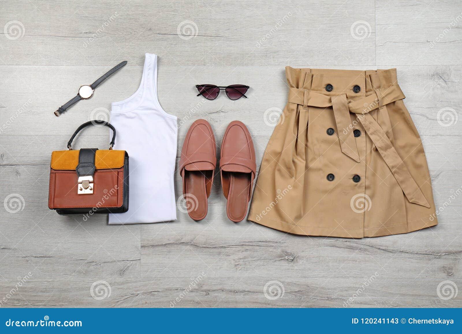 Uppsättning av stilfull kläder och tillbehör på golvet, lekmanna- lägenhet