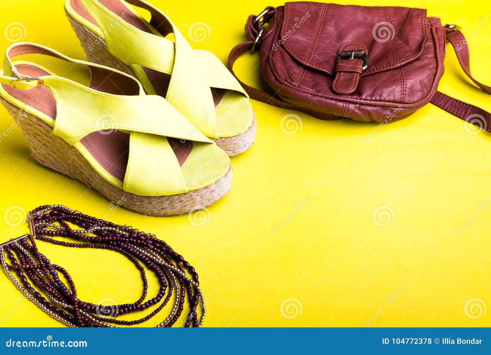 Uppsättning av tillbehör för saker för kvinna` s till sommarsäsongen Bruna sandaler för påsegulingplattform, halsband Lekmanna- l