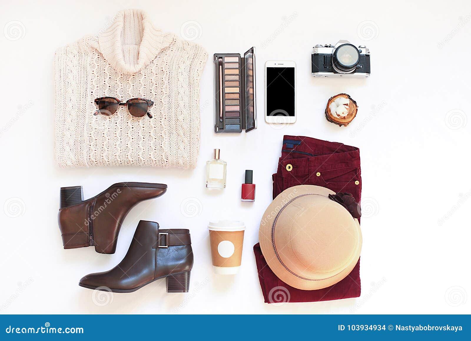 Uppsättningen av kvinnlig stilfull kläder och tillbehören på den vita bakgrundslägenheten lägger, den bästa sikten