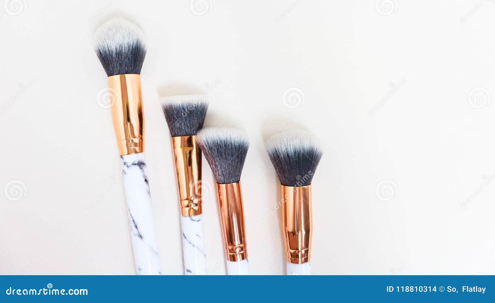 Uppsättningen av makeup borstar på vit färgad komponerad bakgrund
