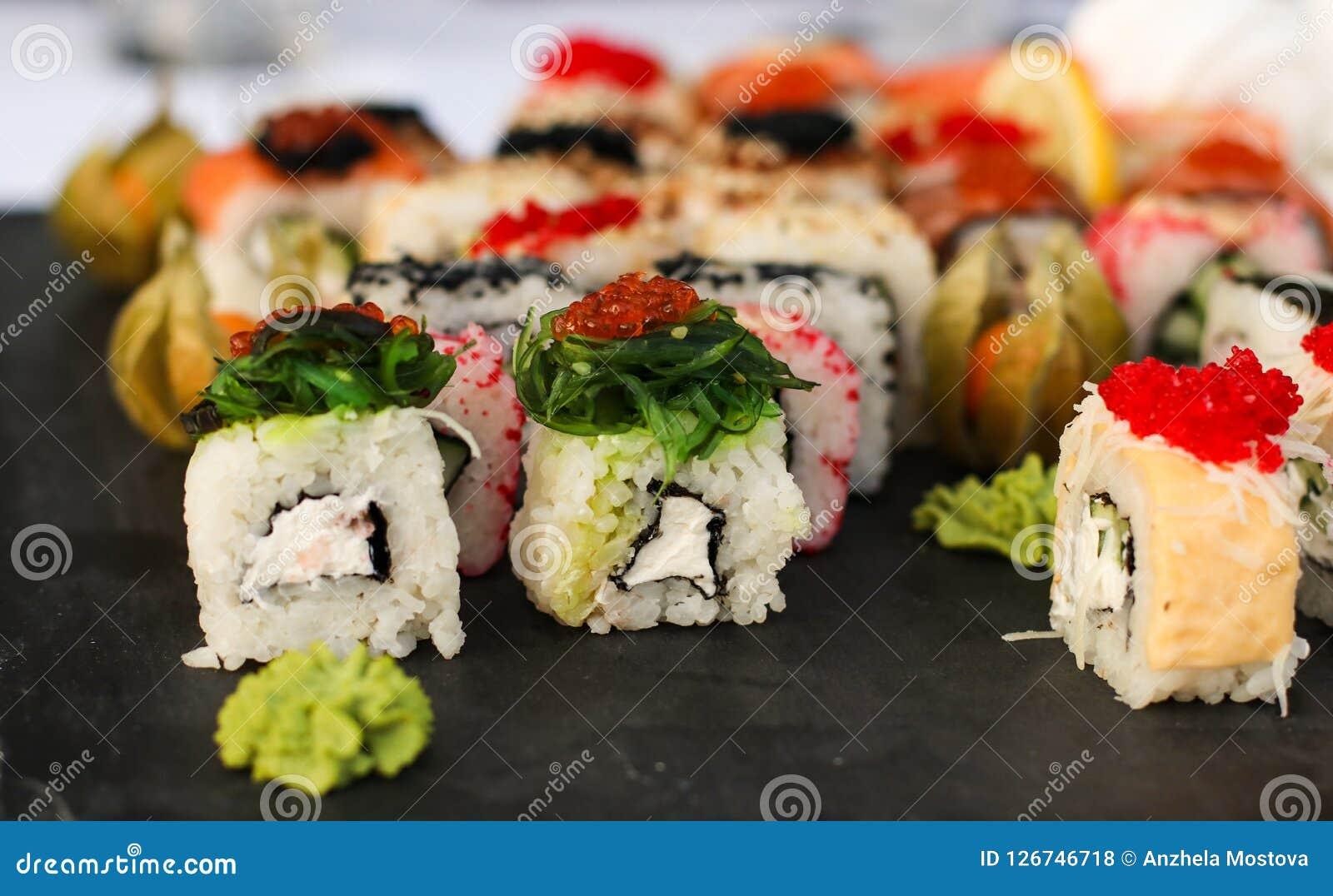 Uppsättningen av sushirullar med vasabi och ingefäran på ett mörker kritiserar plattan