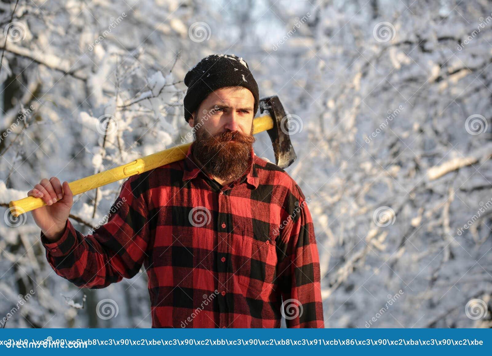Uppsökt man med en handyxa, skogsbruk Stilig man, hipster i snöig skogskogsarbetare i träna med en yxa på