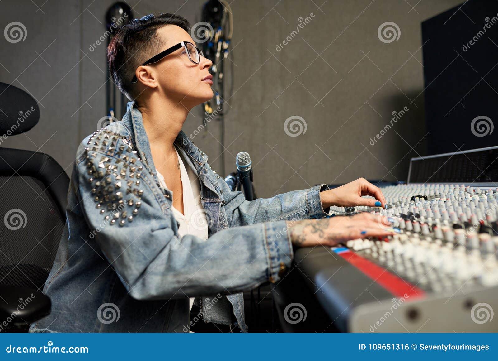 Upptagen kvinnlig ljudsignal tekniker som arbetar i inspelningstudio