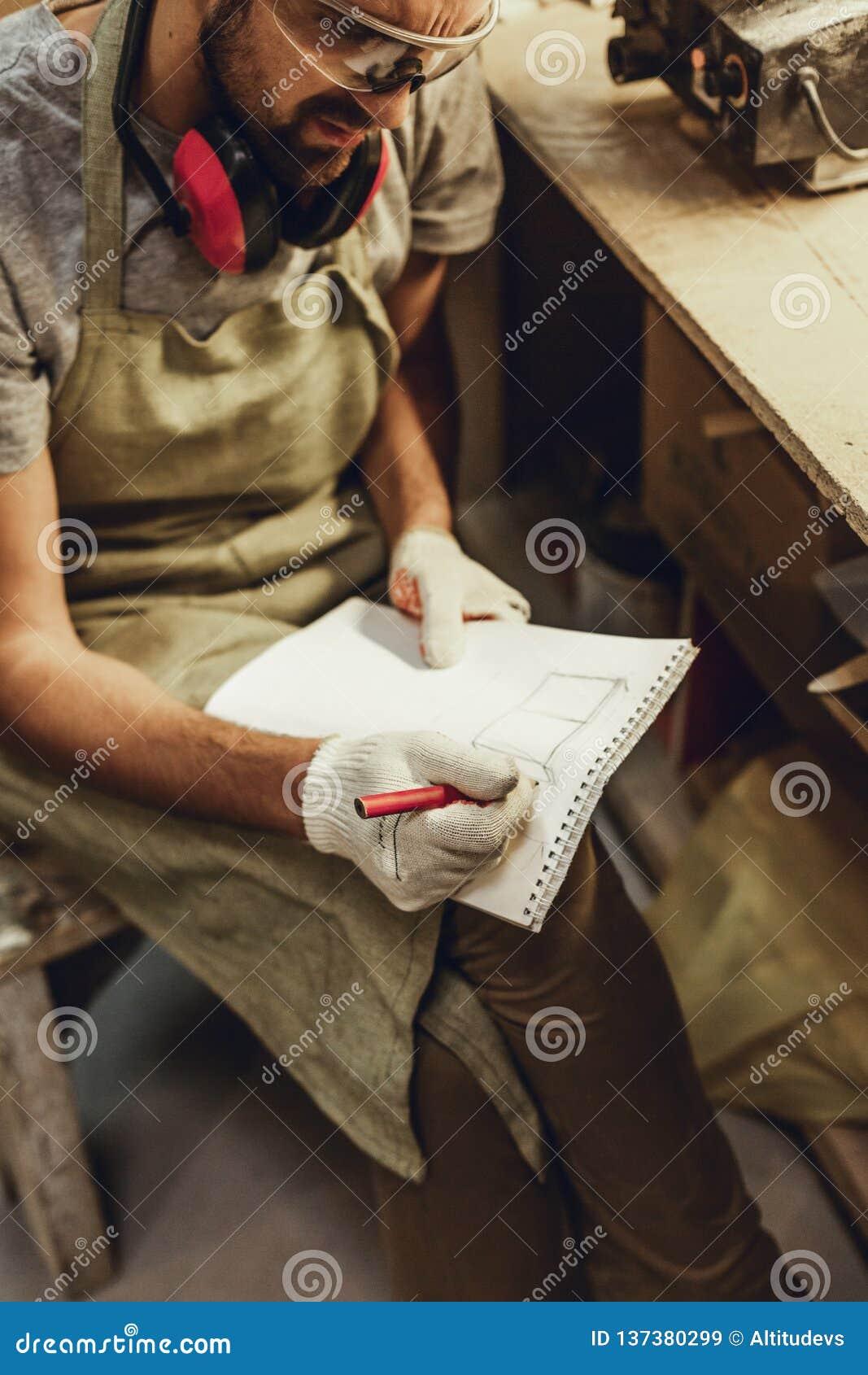 Uprawa rzemieślnik kreśli w notatniku
