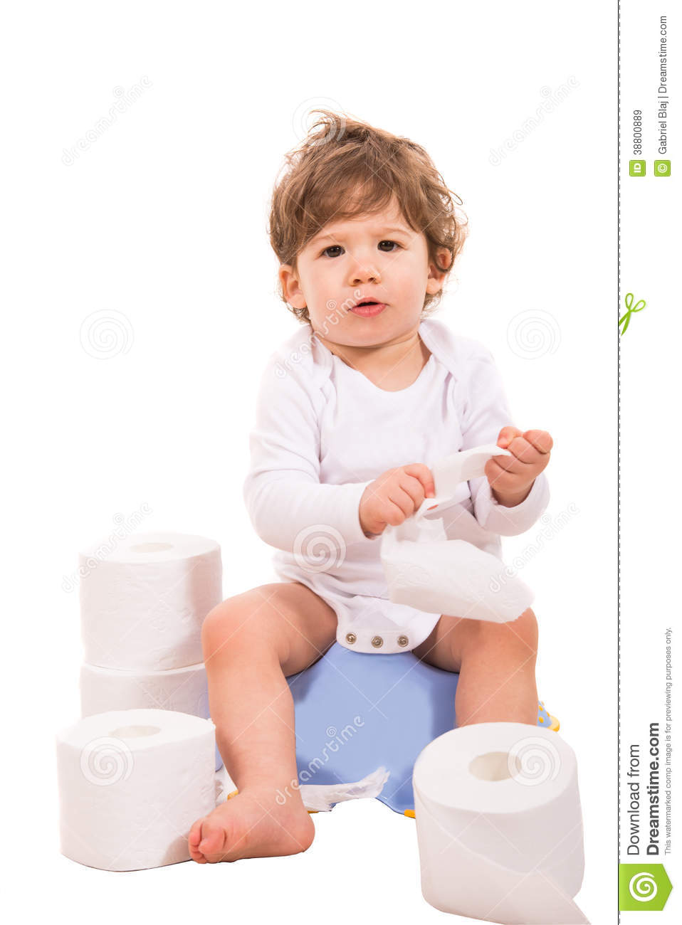 Upset baby boy sitting on potty with rolls of toilet paper around him.