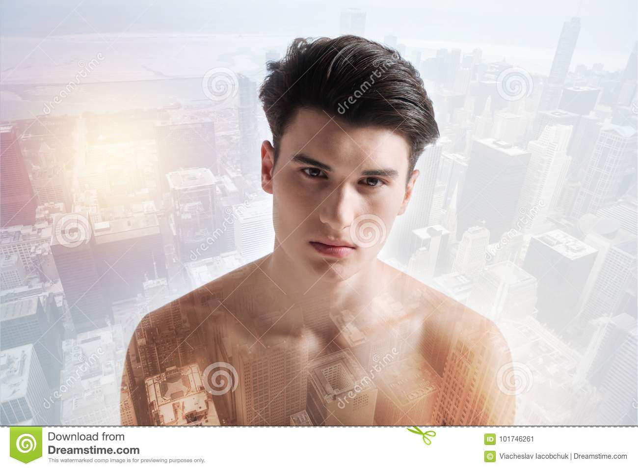 Upset naked boy having sadness in his eyes while standing against urban  background